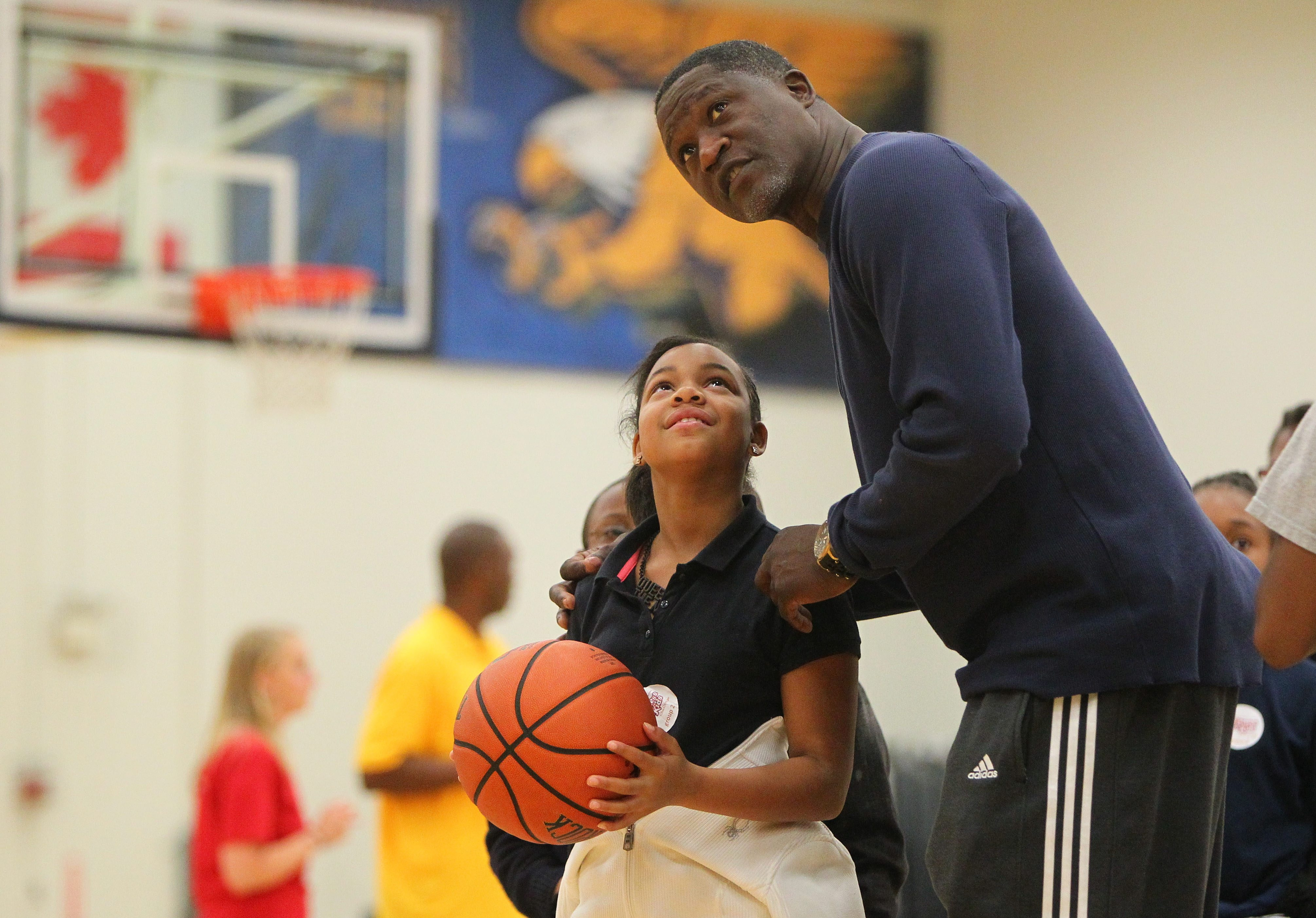 Hall of Famer Dominique Wilkins gives shooting guidance to Enjoli Walerot at Canisius College.