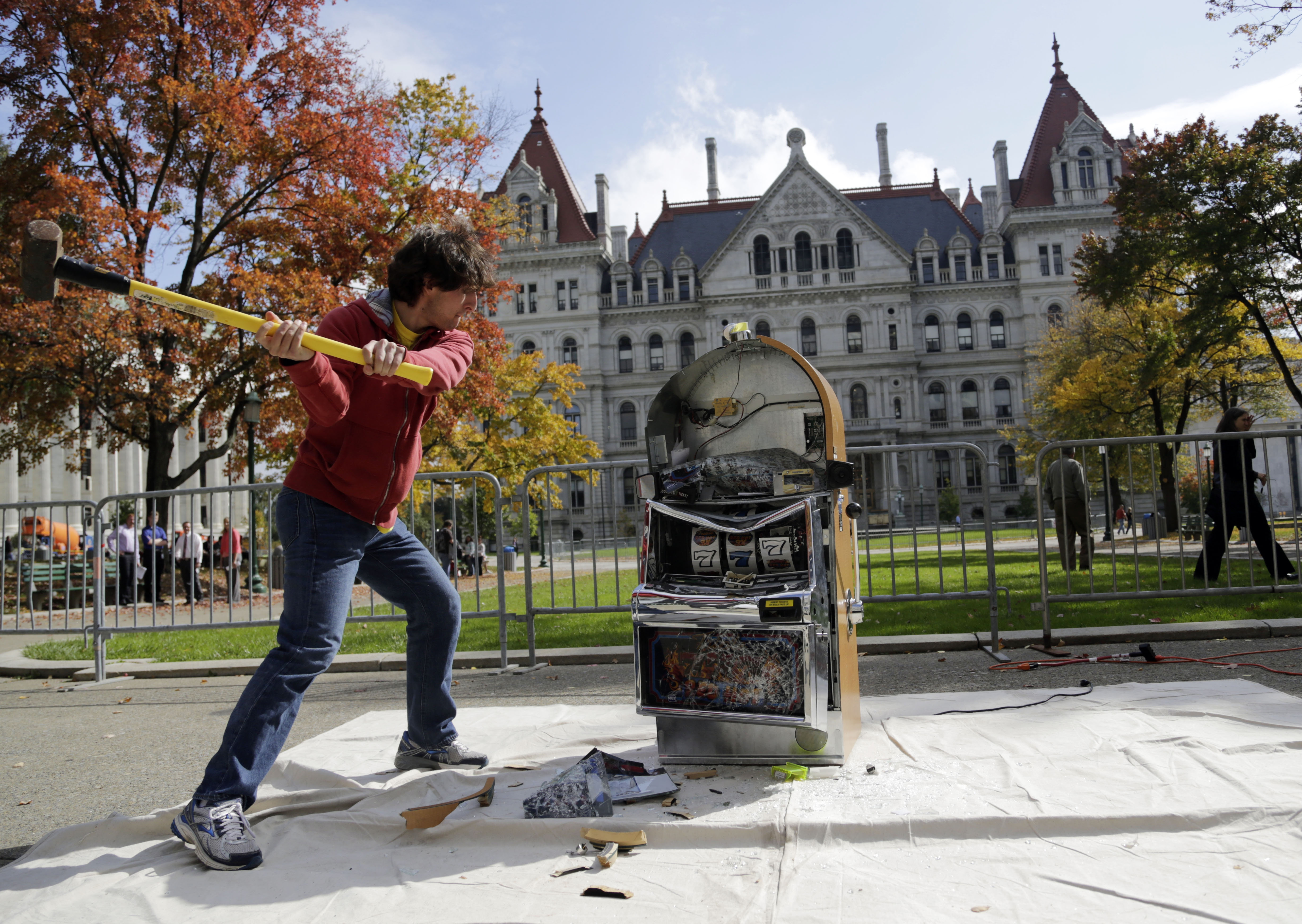 Bill Sisk of the Rockefeller Institute of Government smashes a slot machine with a sledge hammer during an anti-casino event outside the state Capitol today.