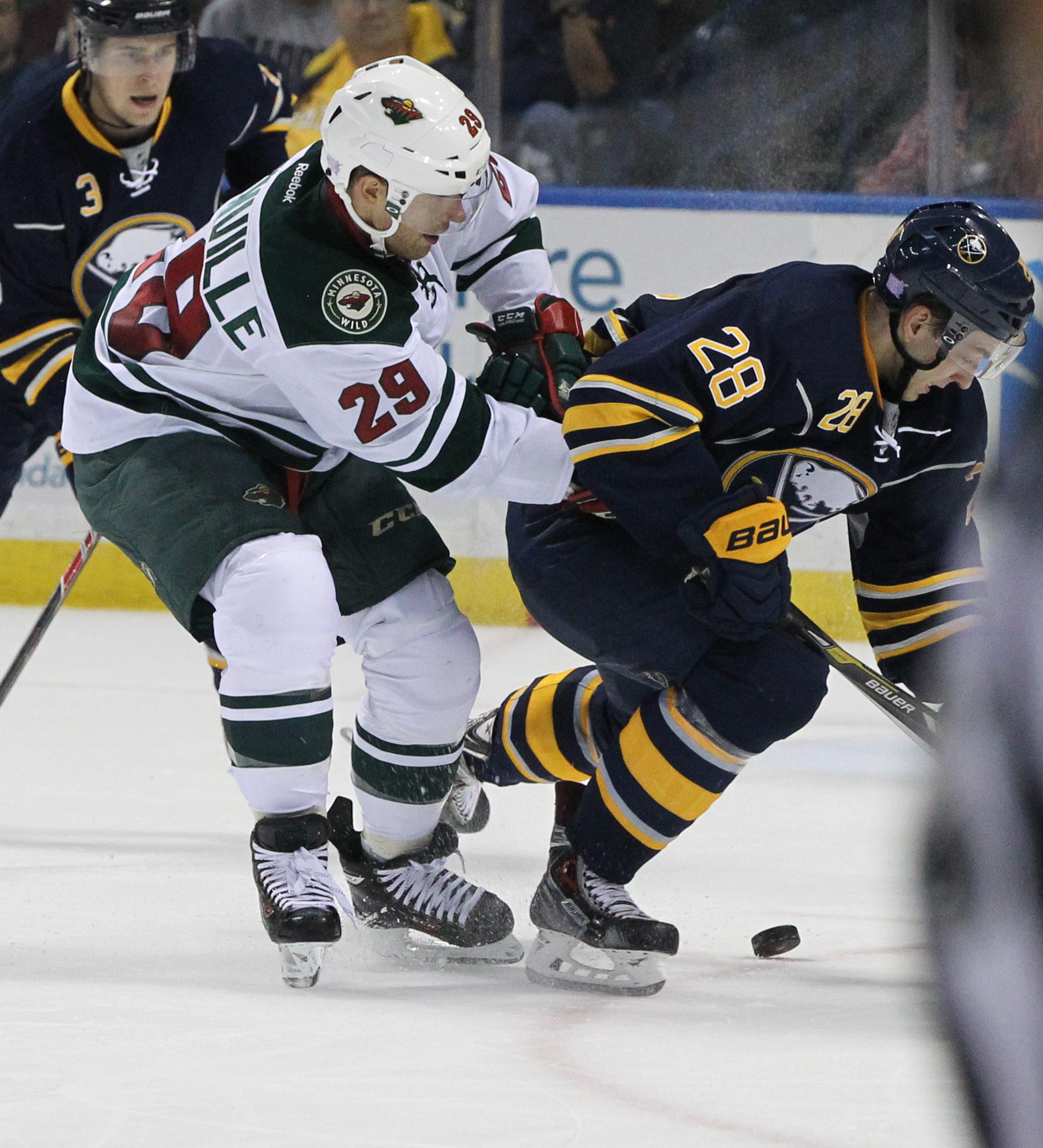 Ex-Sabres captain Jason Pominville of the Minnesota Wild checks Sabres rookie Zemgus Girgensons.  (James P. McCoy/ Buffalo News)