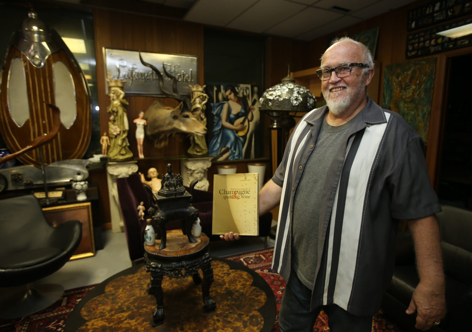 Hank Sontag, owner of Horsefeathers Architectural Antiques and Hollywood Hank's, stands amid the antique furniture and vintage memorabilia inside the store's champagne lounge.