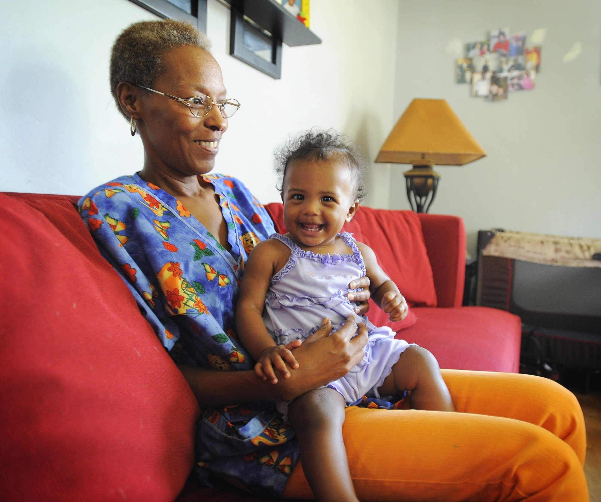 Madie Green, 55, is a self-employed family childcare provider who has no set retirement plan. She also is raising her two grandchildren and is worried about her ability to eventually retire. Here, she holds onto 8-month-old Logan Proctor, one of the children she cares for on weekdays, August 6, 2013, at her District Heights, Maryland home. (Erin Kirkland/Baltimore Sun/MCT)