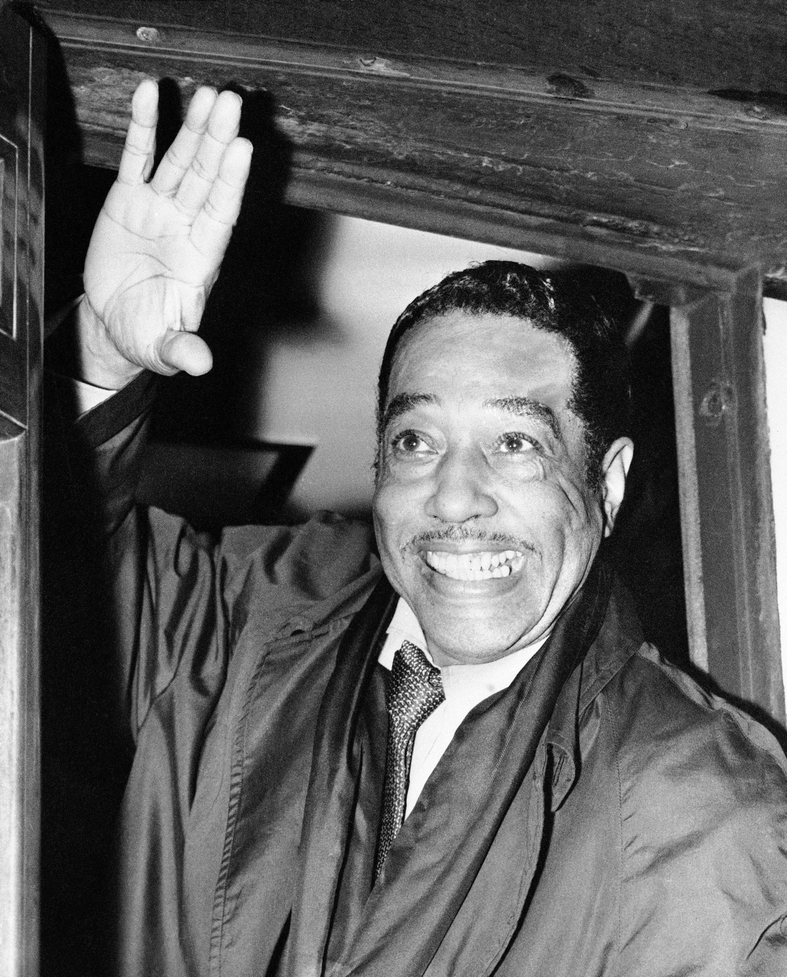 At left,  Duke Ellington waves to fans when he arrives in London in 1958. Charlie Parker, right, in an undated photo. Two new biographies shed light on the personalities of the jazz icons.