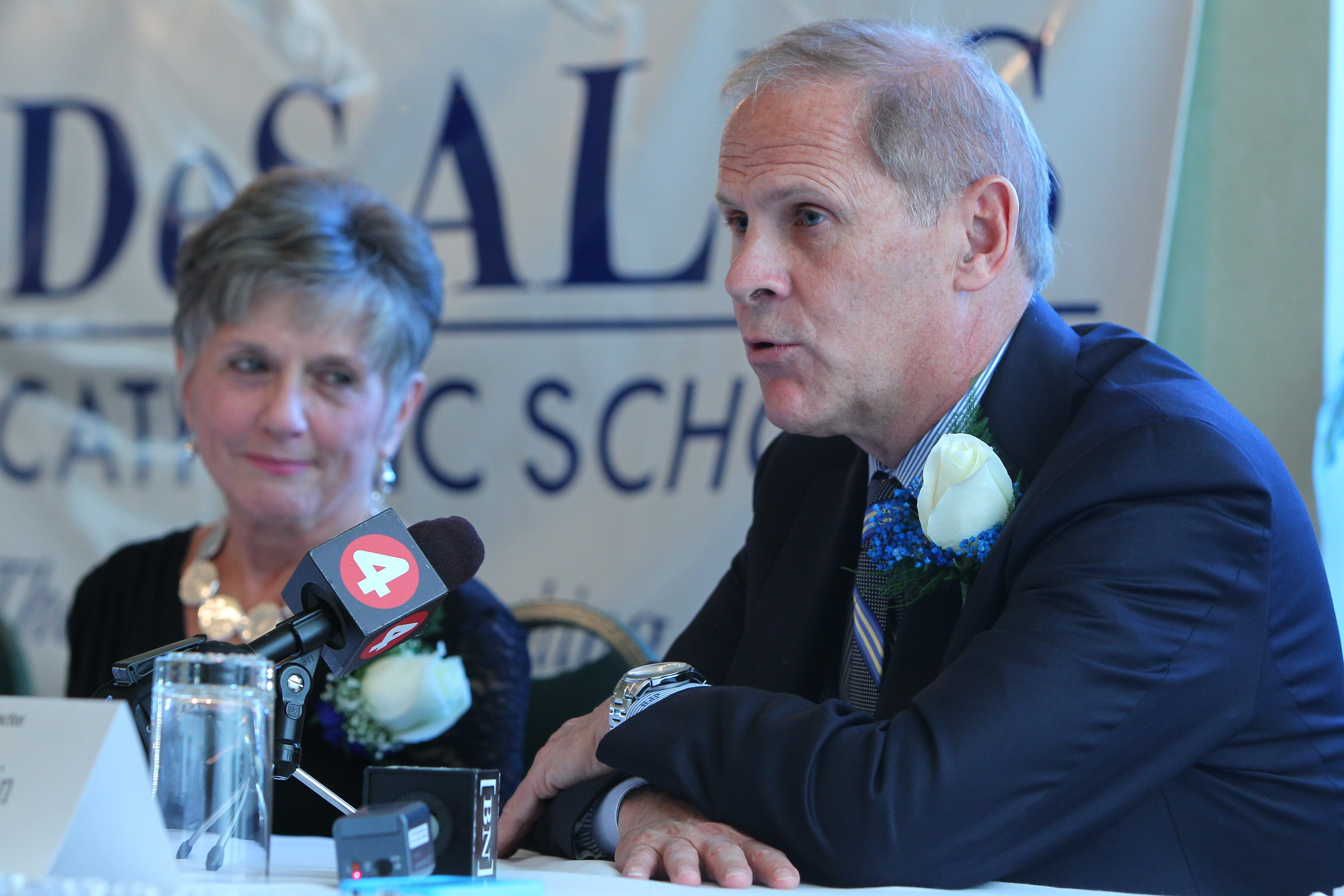 Michigan men's basketball coach John Beilein speaks to the media with others after being inducted into the DeSales Hall of Fame.