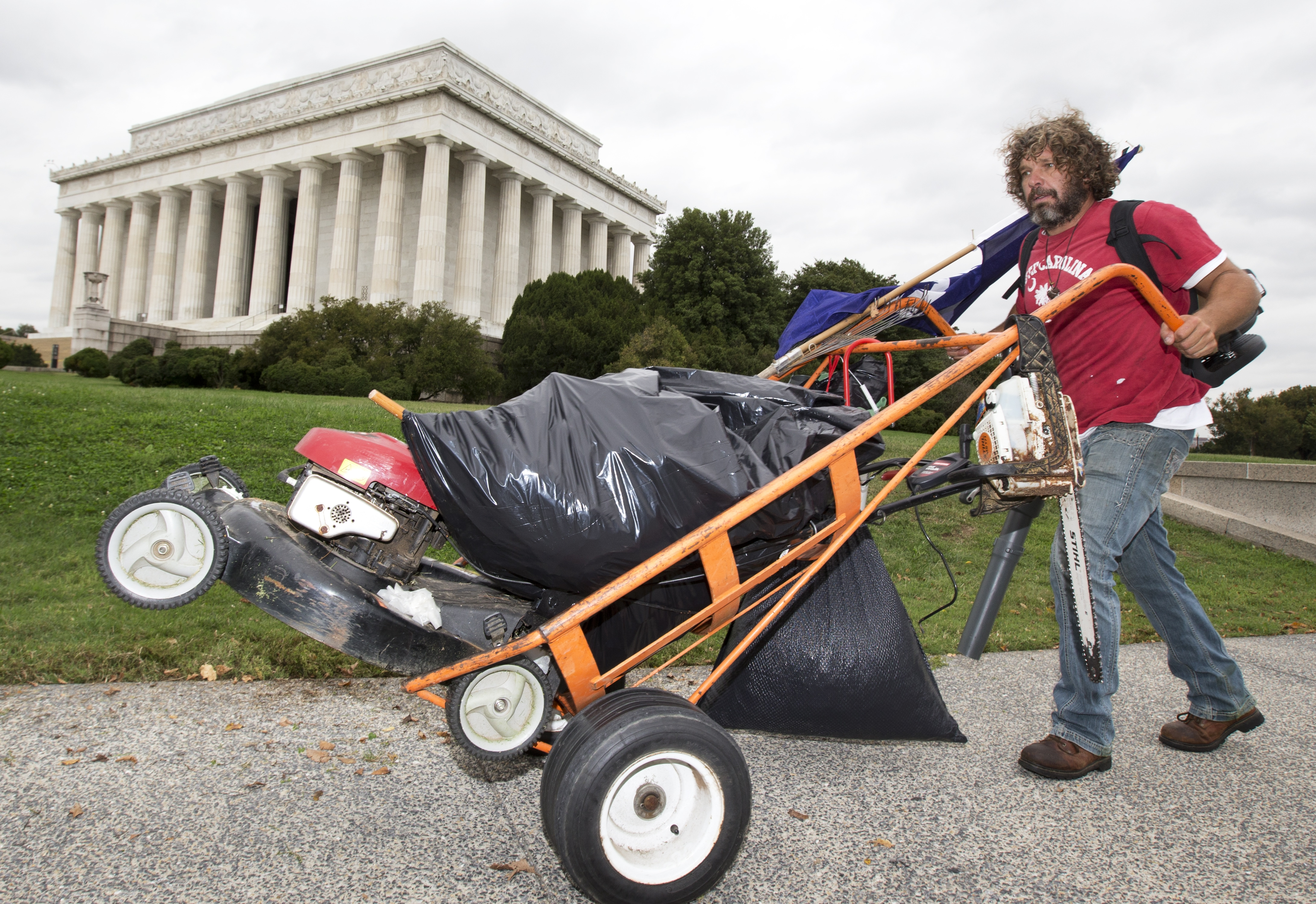 Chris Cox of Mount Pleasant, S.C., pushes a cart near the Lincoln Memorial on Wednesday.  Cox has taken it upon himself to clean up the grounds around the Lincoln Memorial during the government shutdown.