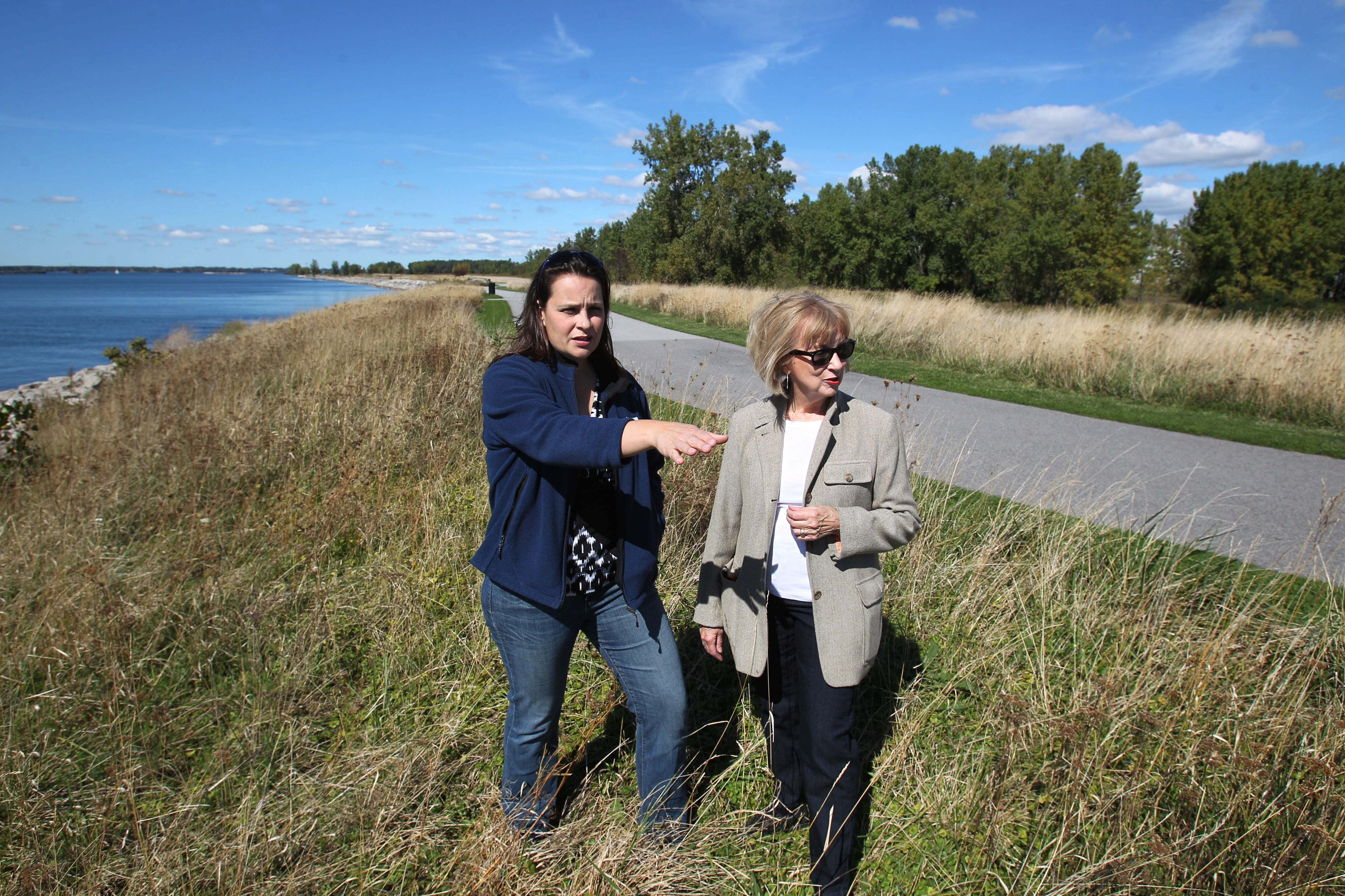 Jill Jedlicka, executive director of Buffalo Niagara Riverkeeper, left, and Joanne Kahn, who chairs the 21st Century Park on the Outer Harbor, walk along the piece of outer harbor land adjacent to the Bell Slip. The two groups are promoting a large park in this area for hiking, walking and water activities.  Sharon Cantillon/Buffalo News file photo