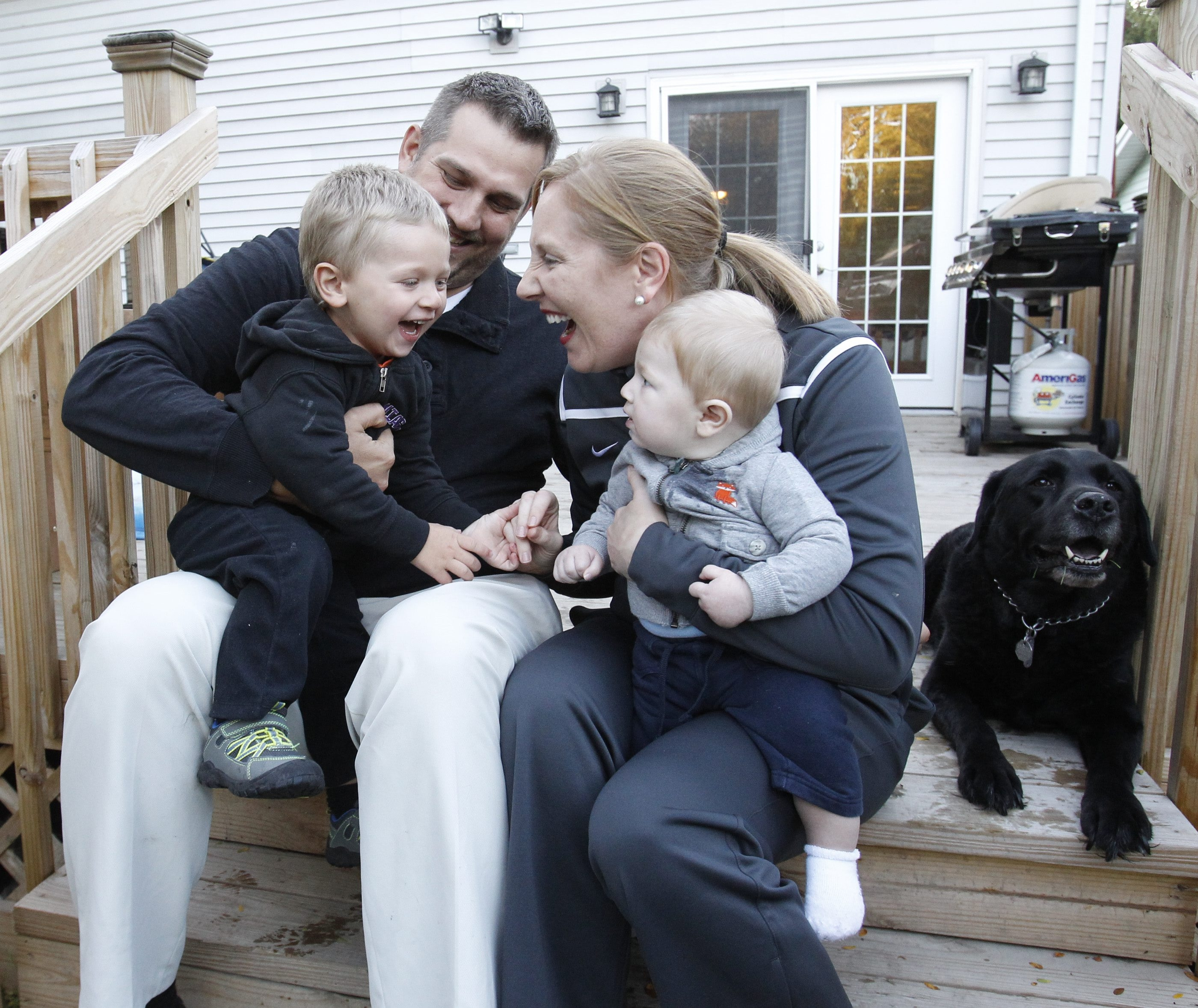 Niagara women's basketball coach Kendra Faustin has some family time at home, with her sons Cal and Blake, who is being held by Faustin's husband RJ. The family dog is Mason.