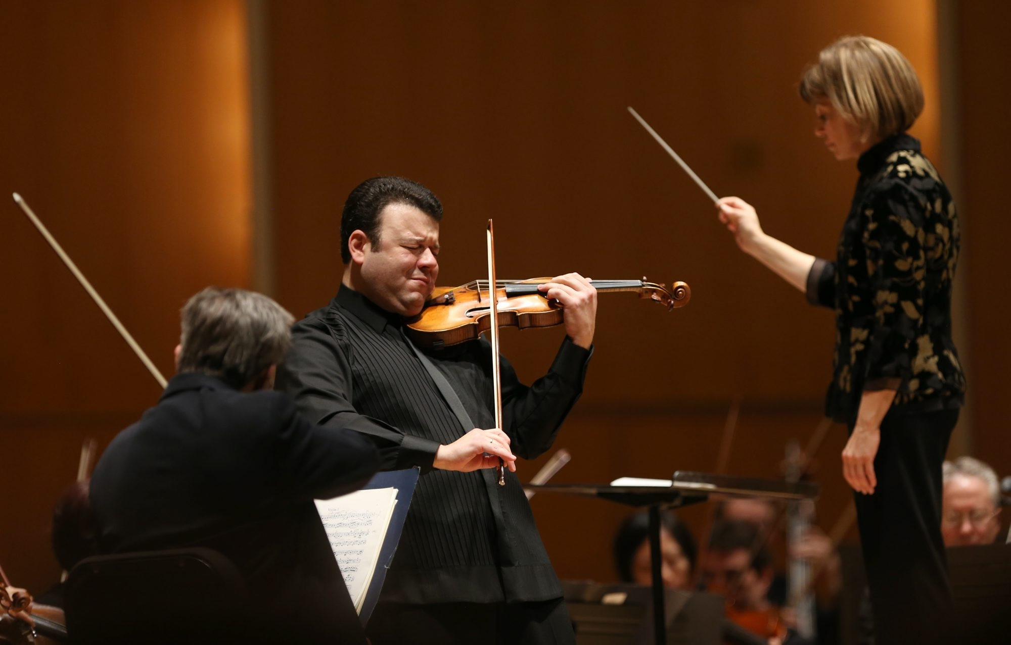 Violin virtuoso Vadim Gluzman, left, performs as conductor JoAnn Falletta leads the Buffalo Philharmonic Orchestra in a special Brahms concert Friday at Kleinhans.
