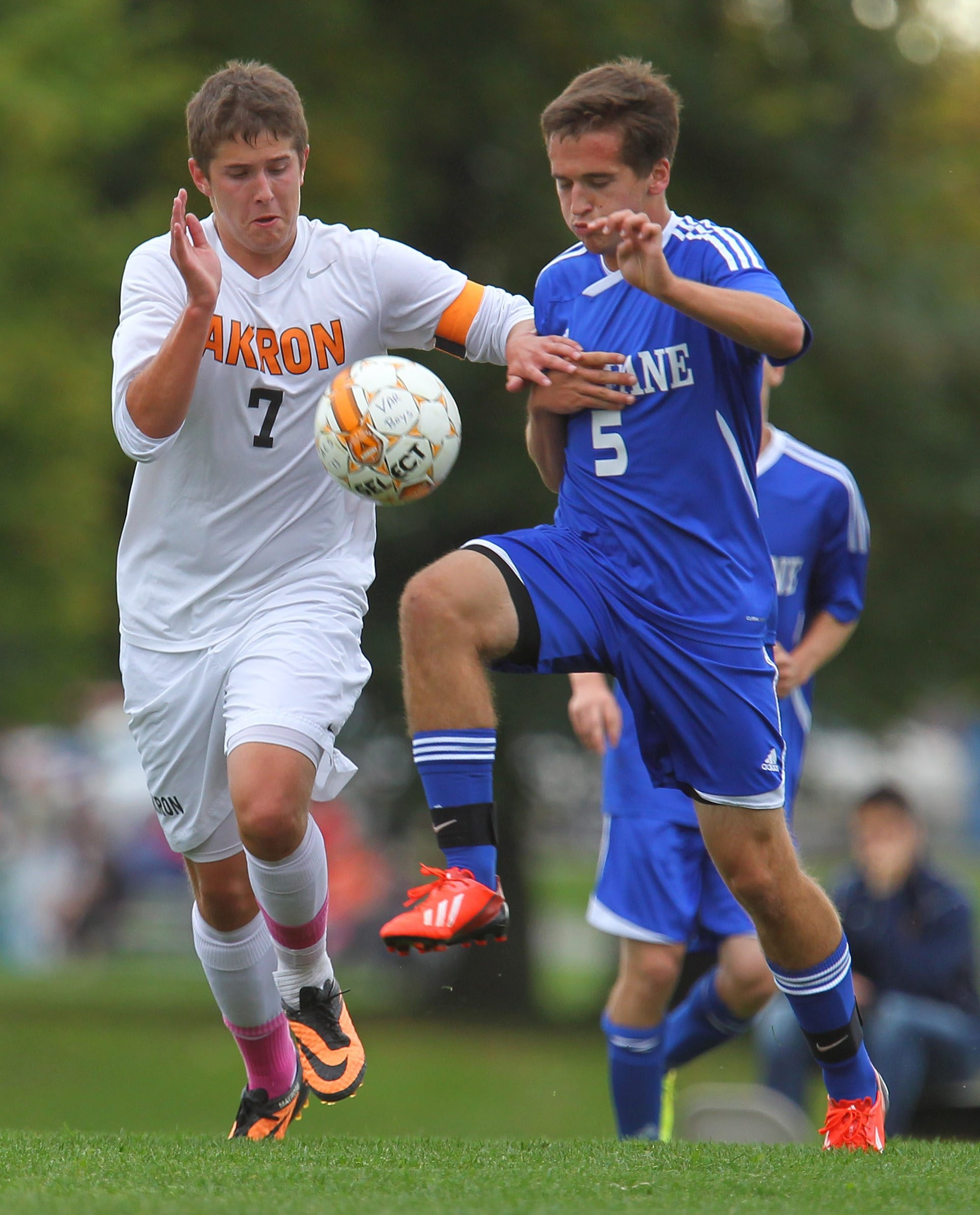 Akron's Chris Mayrose (7) battles for a loose ball with Newfane's Mike Lekanka during a boys soccer match at Akron on Thursday. Akron won, 3-0.
