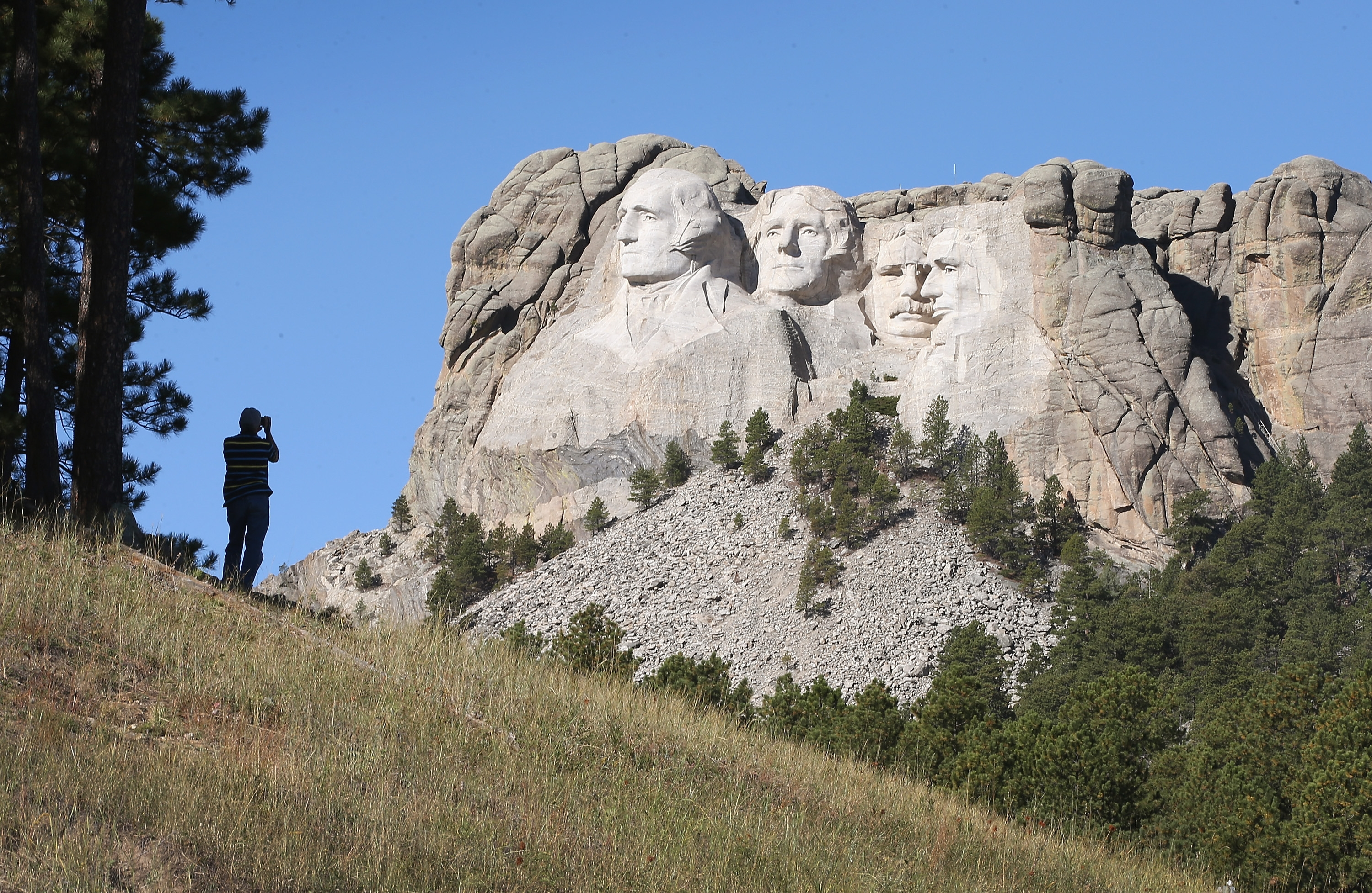 A tourist takes a photo of Mount Rushmore National Memorial from outside the park Tuesday. A group of local tourists was turned away from the site Wednesday.