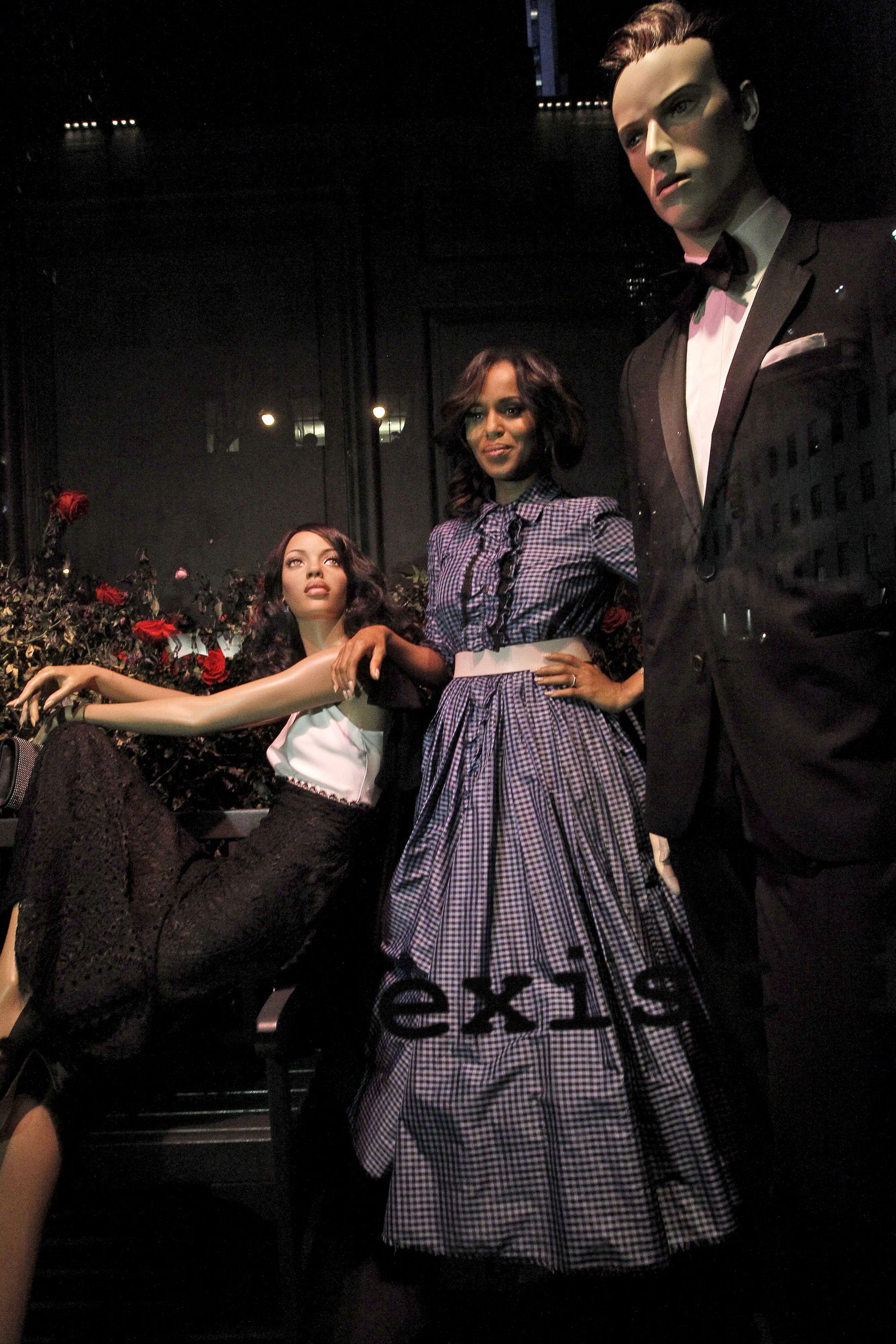 """Kerry Washington poses between mannequins honoring her TV series, """"Scandal,"""" at Saks Fifth Avenue."""