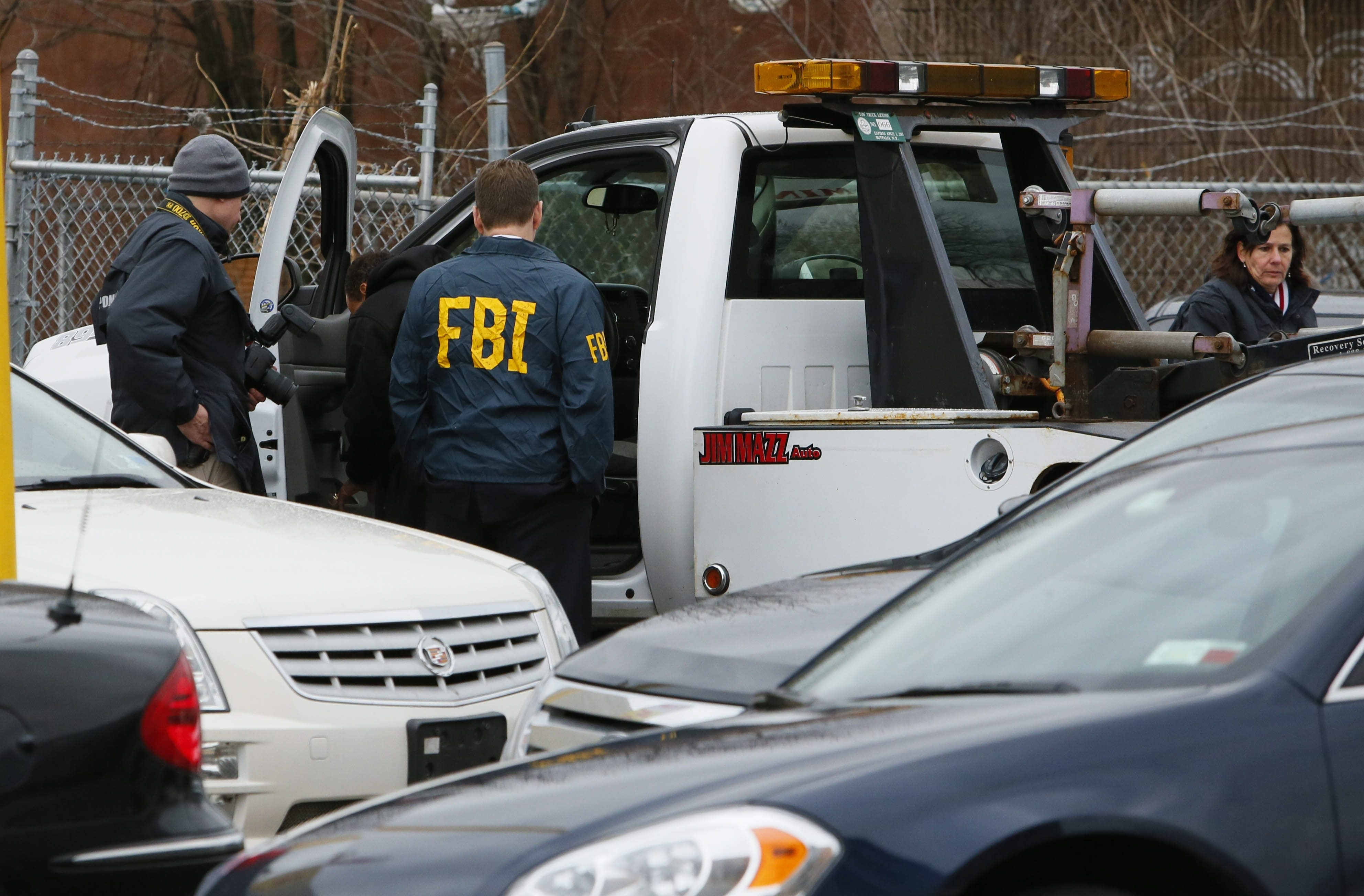 Members of the FBI evidence response team collect evidence while executing a search warrant in December at Jim Mazz Auto on Bailey Avenue in the city's Lovejoy neighborhood. Jim Mazzariello, the owner of Jim Mazz Auto, was indicted Wednesday on felony charges of bribery and filing false tax returns.