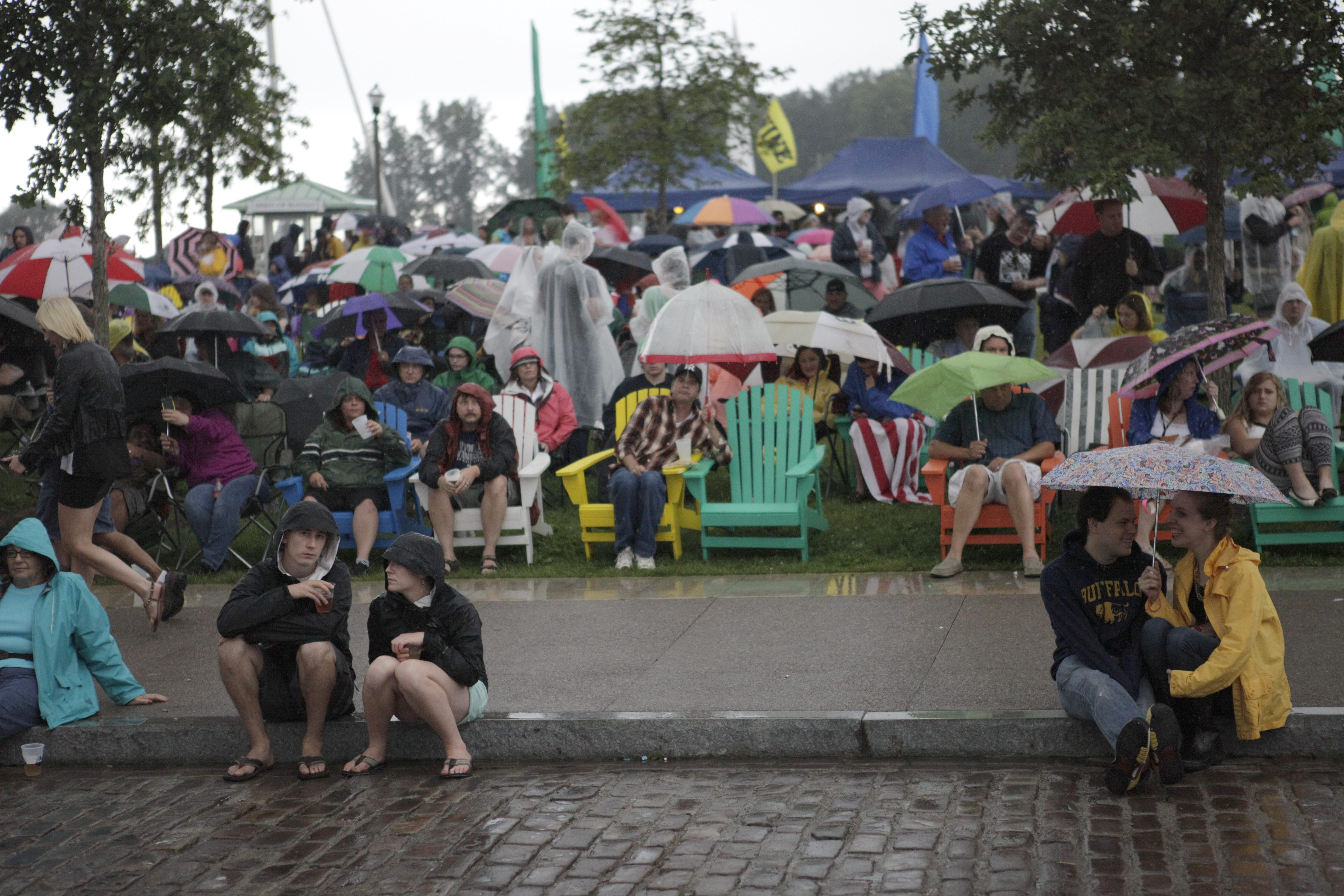 Concertgoers take cover under umbrellas at Buffalo Place Rocks Canalside in June.