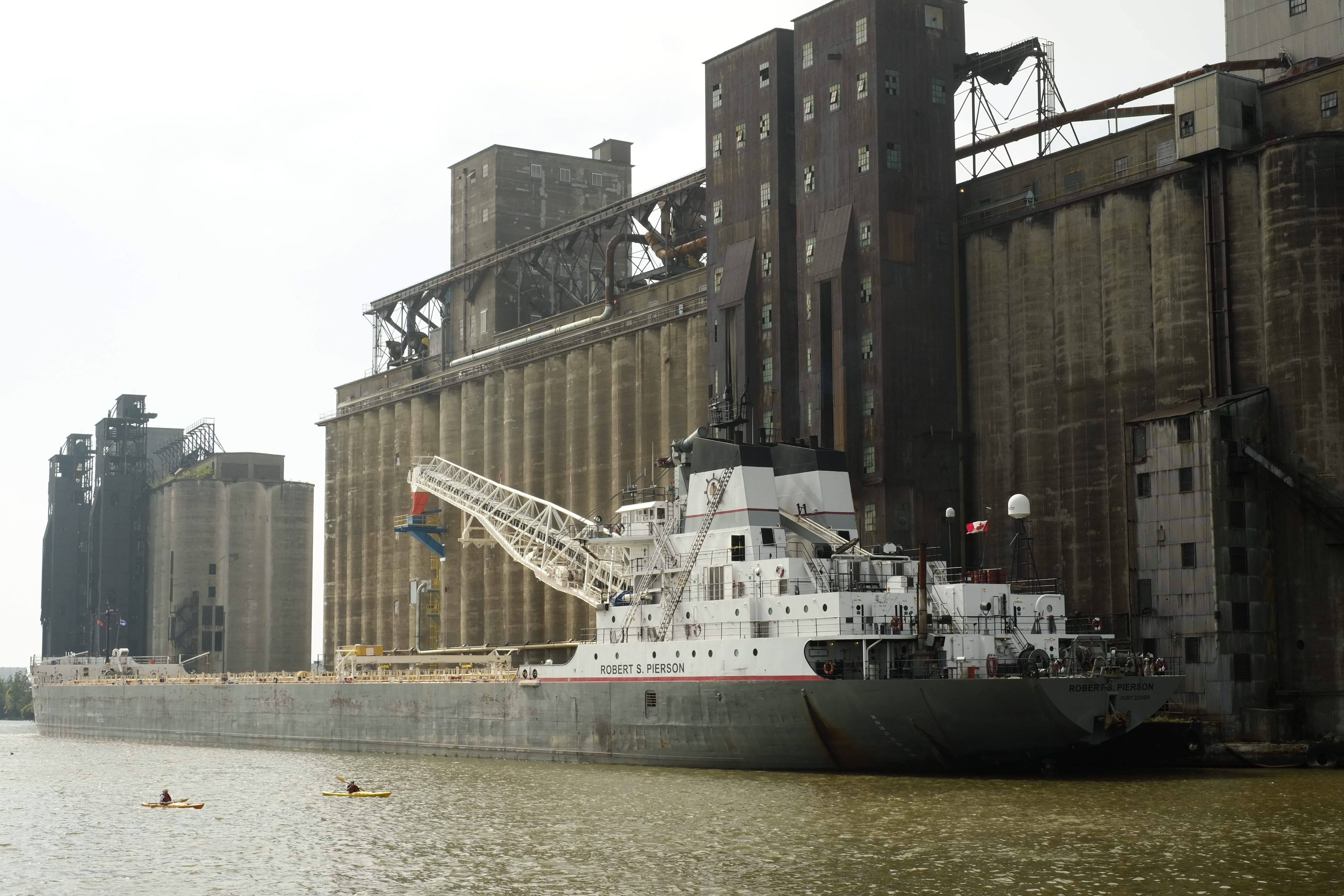 Kayakers pass the freighter Robert S. Pierson as it unloads grain Tuesday. The freighter arrived in Buffalo on Friday but had to wait until Tuesday to deliver its cargo because of the broken Ohio Street lift bridge.  See more photos at BuffaloNews.com/galleries.