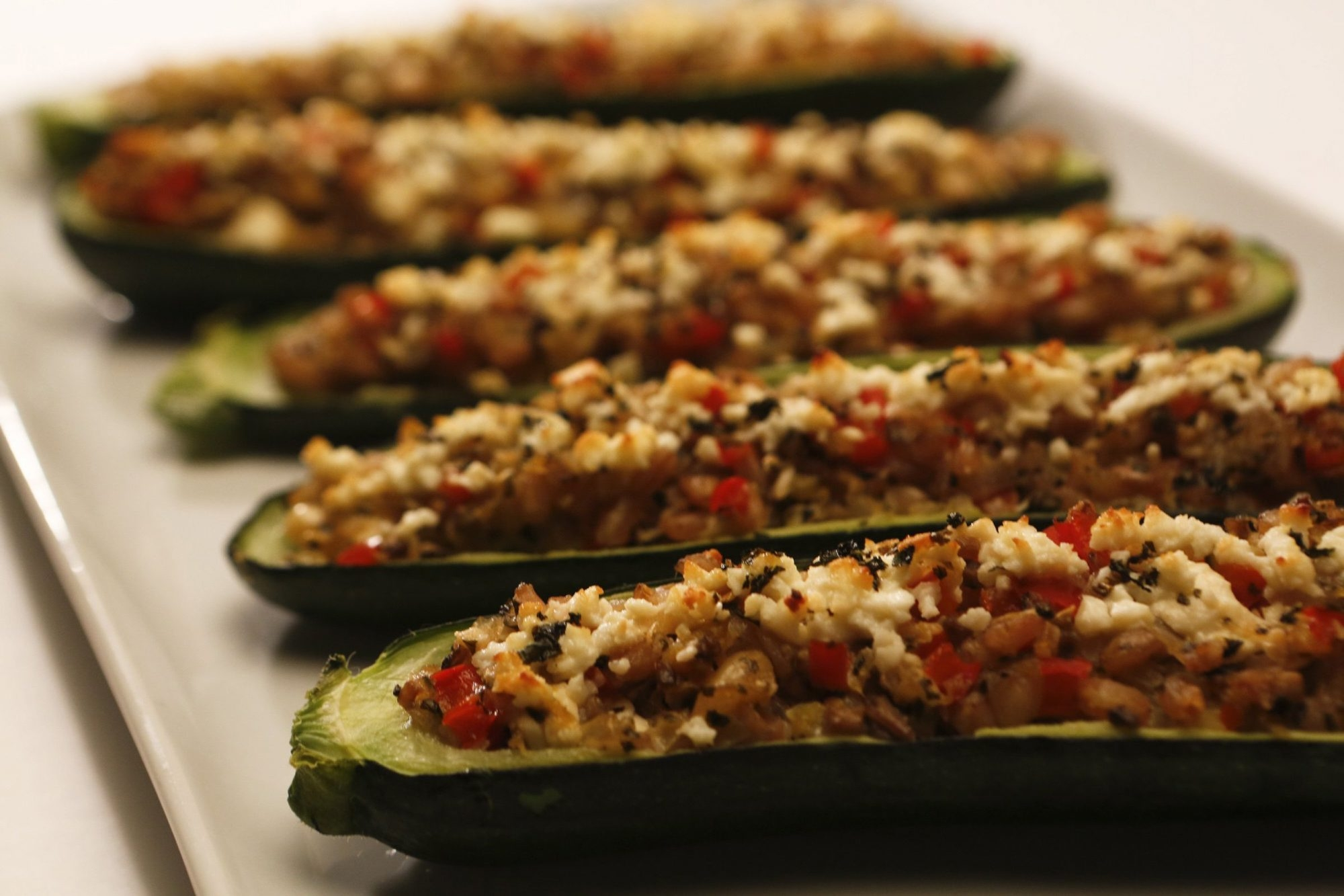 When your garden gives you an abundance of zucchini, scoop them out and stuff with farro, red pepper and feta.