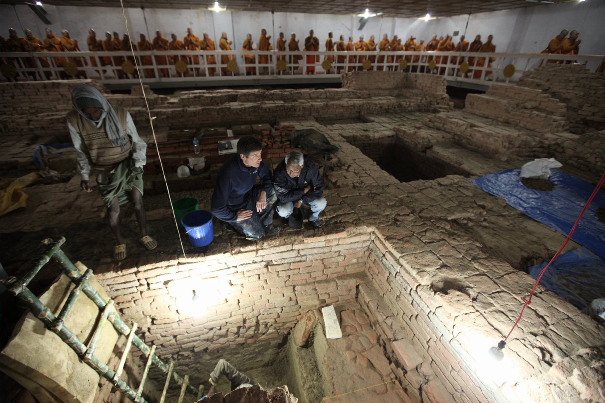 Archaeologists Robin Coningham, second from right, and Kosh Prasad Acharya, right, look over excavations within the Maya Devi Temple at Lumbini in Nepal.
