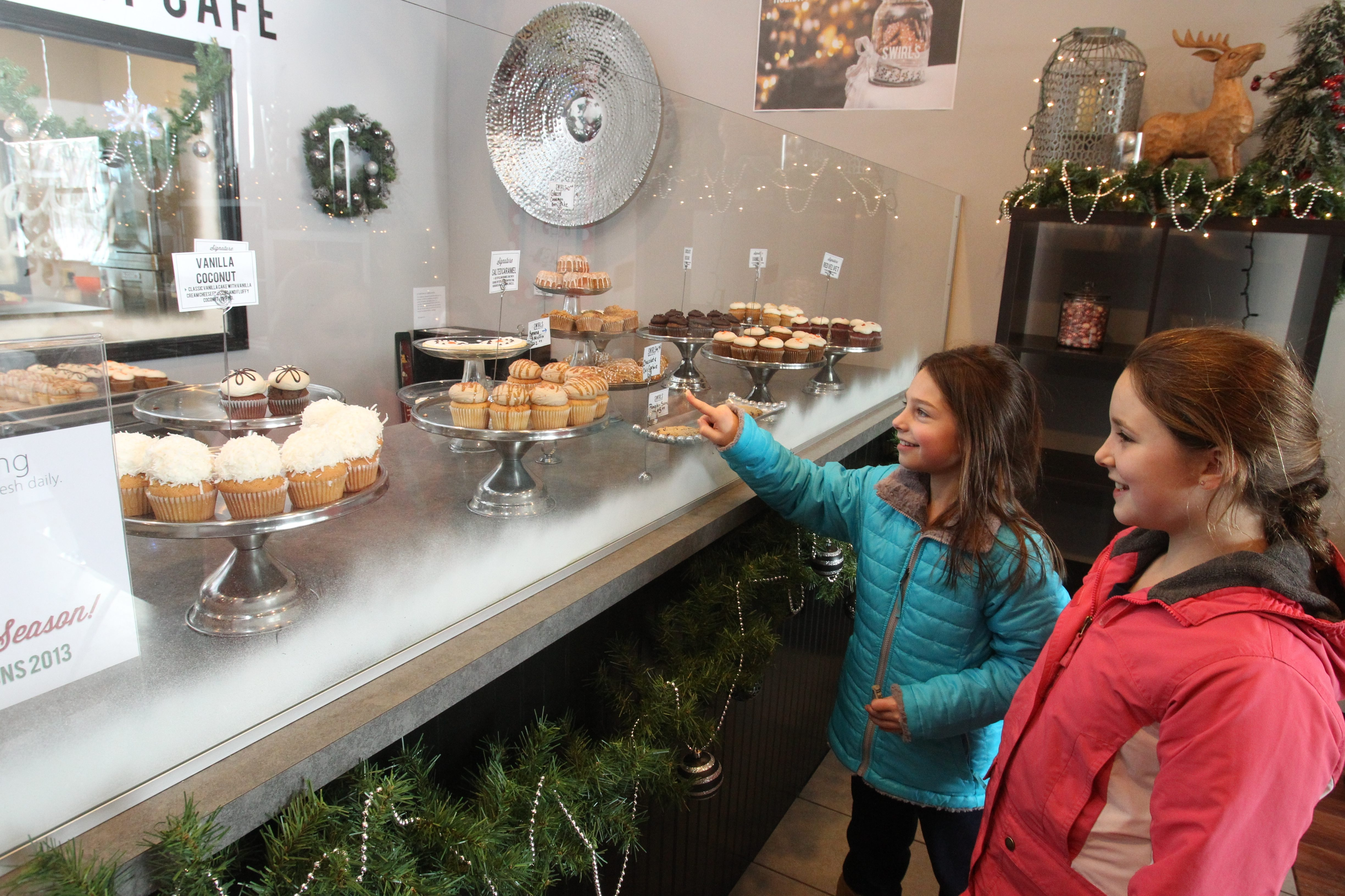"""Alexa Hausaner, 10, picks a cupcake as Kayla Baines, 9, looks on at Swirls Market Cafe in East Aurora on """"Small Business Saturday."""""""