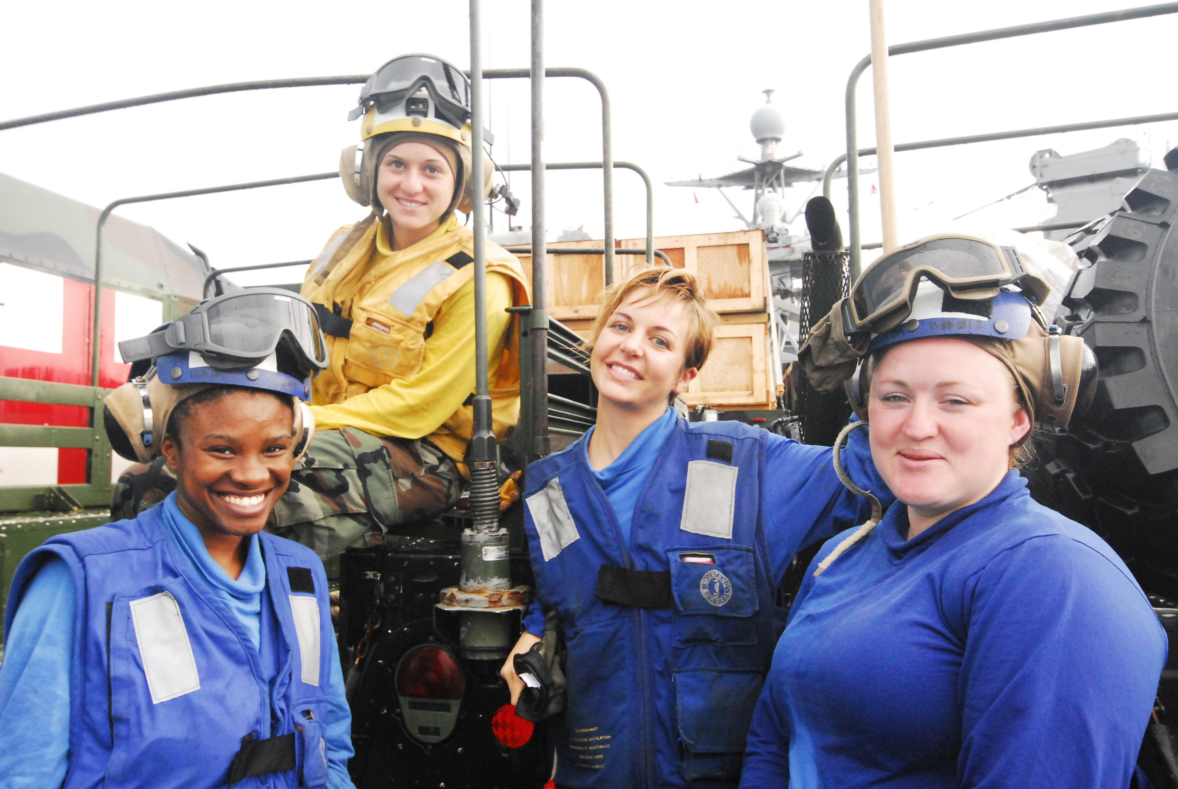 Airman Jennifer L. Confer, top, with members of her Flight Deck Crew between air operations aboard the USS Ashland.