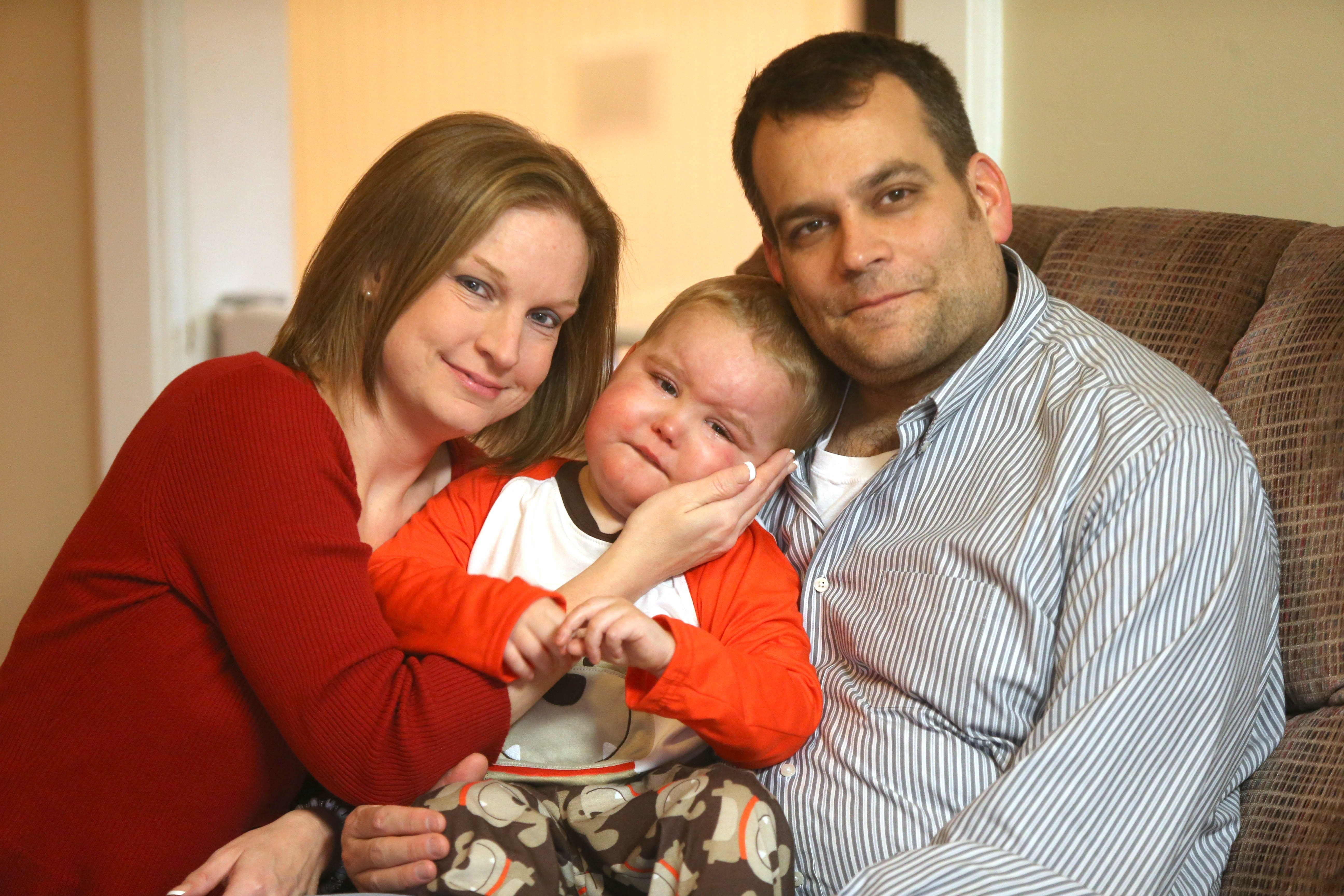 Dawn and Chad Millen hold their son, John, 3, in their Orchard Park home Friday. Since discovering John has an inoperable brain-stem tumor, the family has tried to live in the moment, enjoying the time they have left with the boy.
