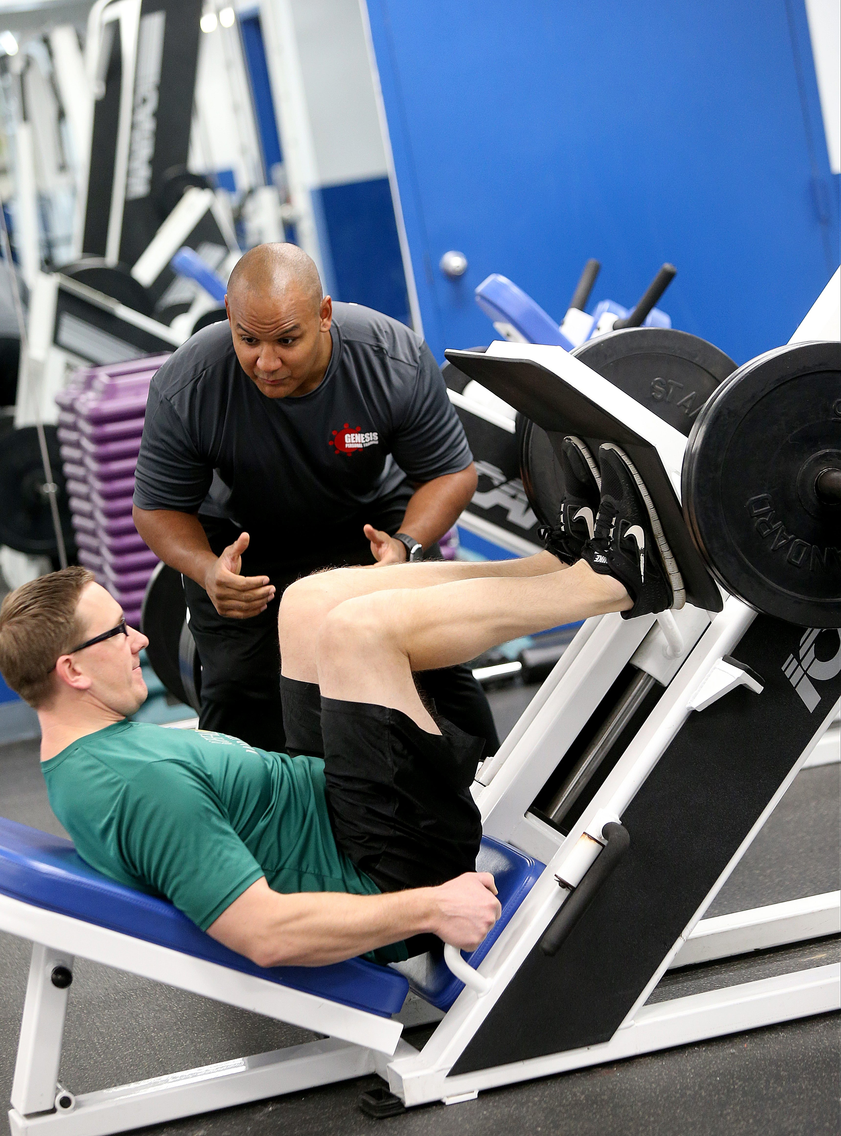 Personal trainer Bryon Sperduti, top, puts Joel Drier through the paces at Genesis Personal Training in West Seneca.
