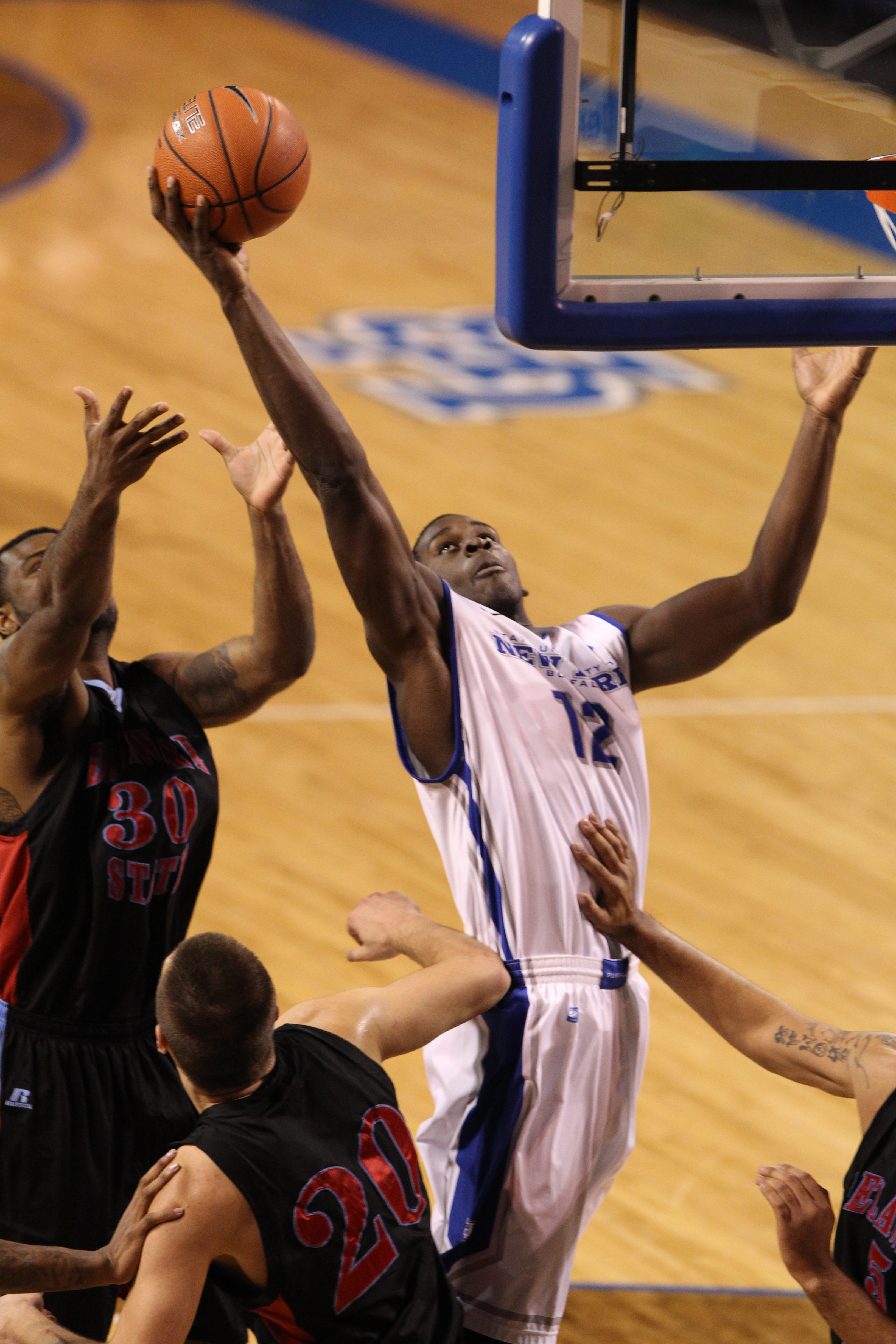 UB's Javon McCrea (12) scores two points over Delaware State's Jordan Lawson (30) in the first half.