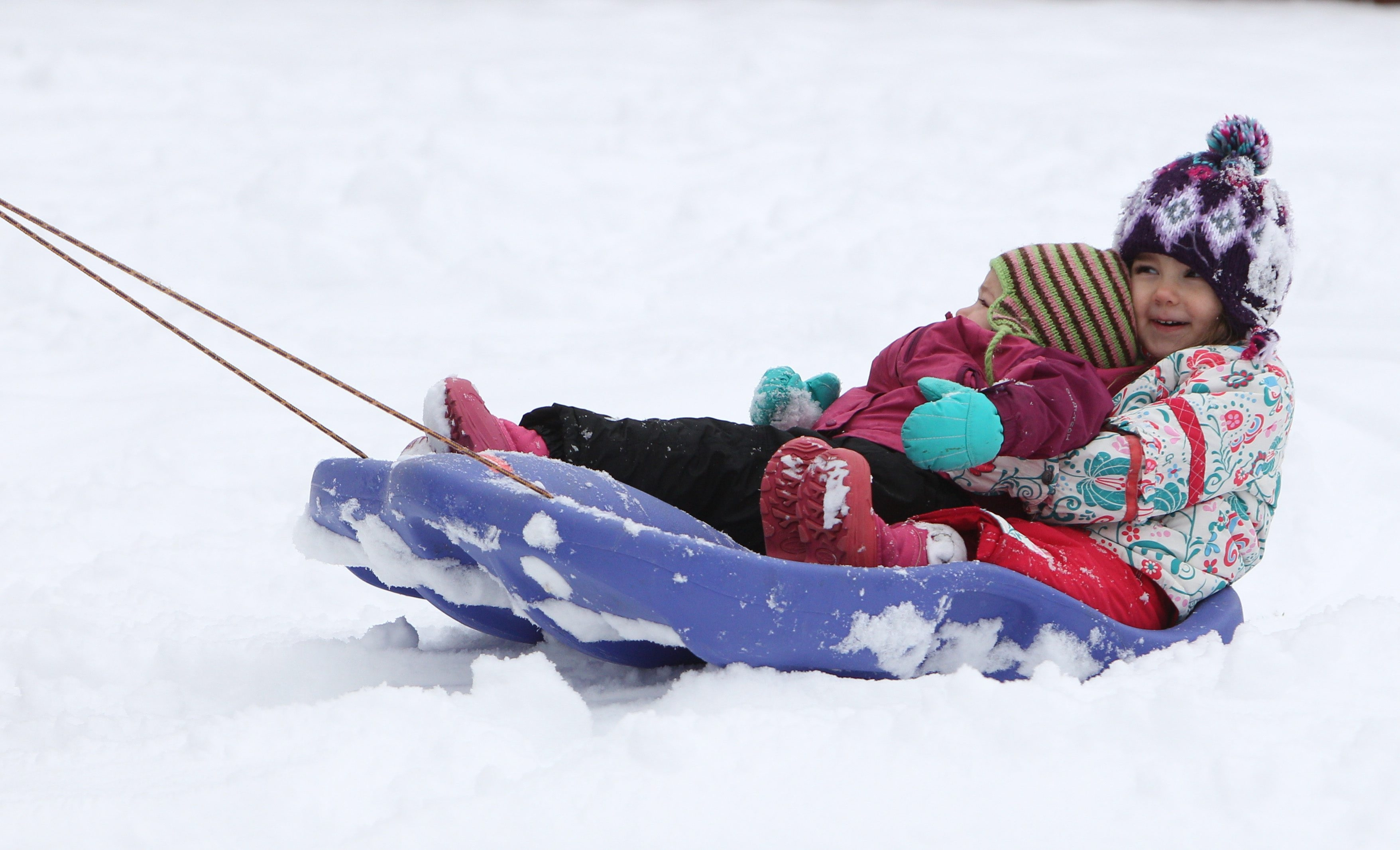 The Rakoski sisters, Gigi, 3, holding Alexandra, 1, enjoy being pulled in their sled by their mother, Nicole.
