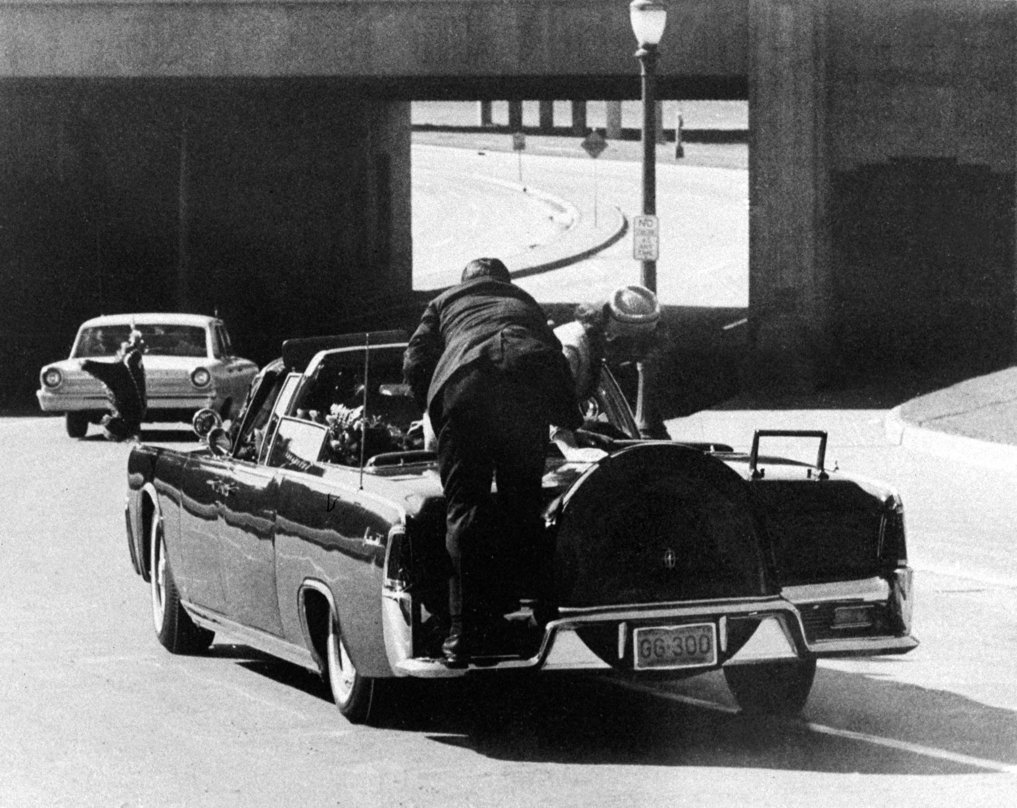 Photo shows Clint Hill climbing on the back of limousine as the first lady climbs out to retrieve what he later realized was brain matter from the slain president.