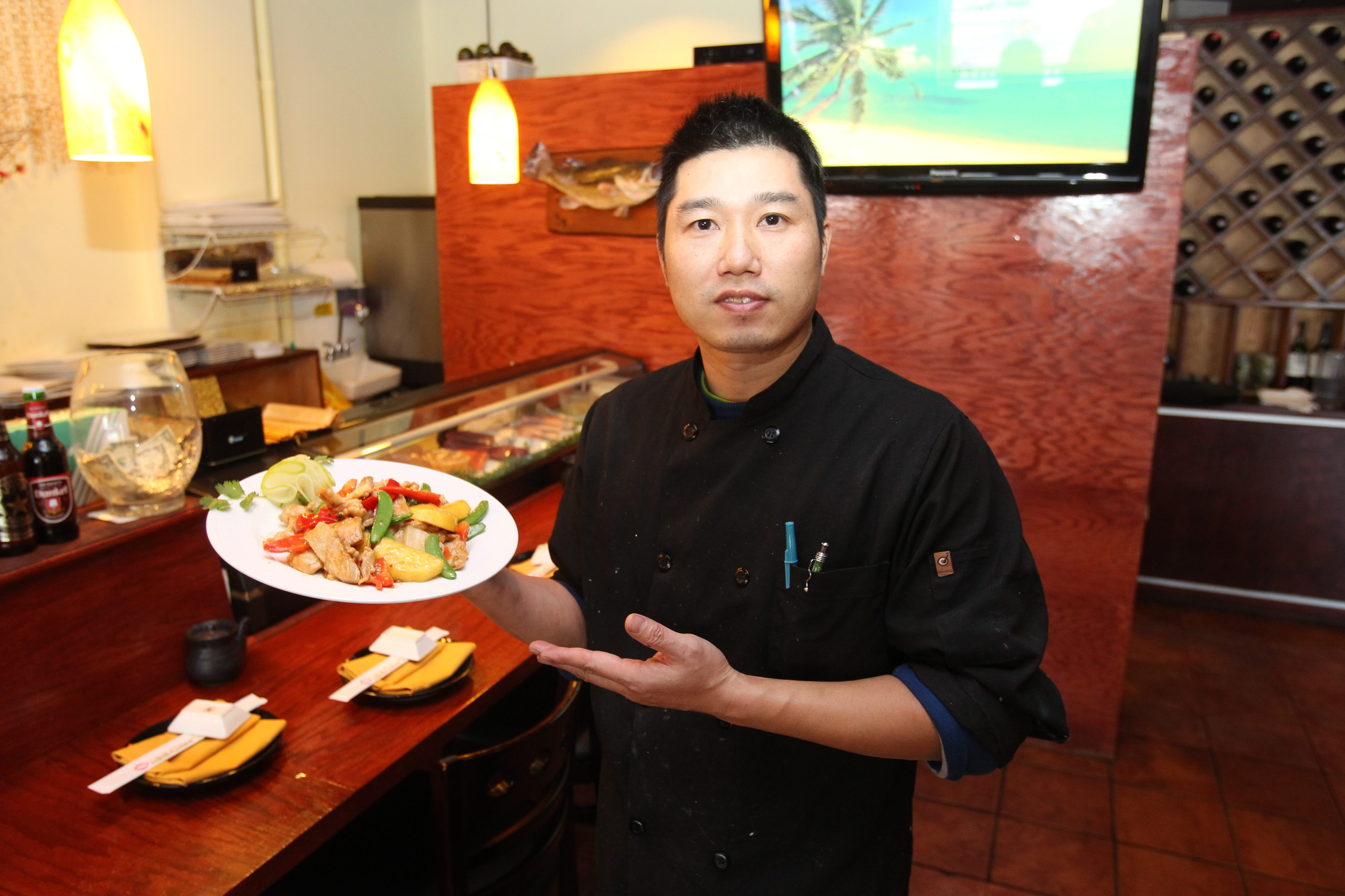 Owner Brandy Dong with the spicy mango chicken entree at Orchid Asian Bistro on 2756 Elmwood Ave in Kenmore. (John Hickey / Buffalo News)