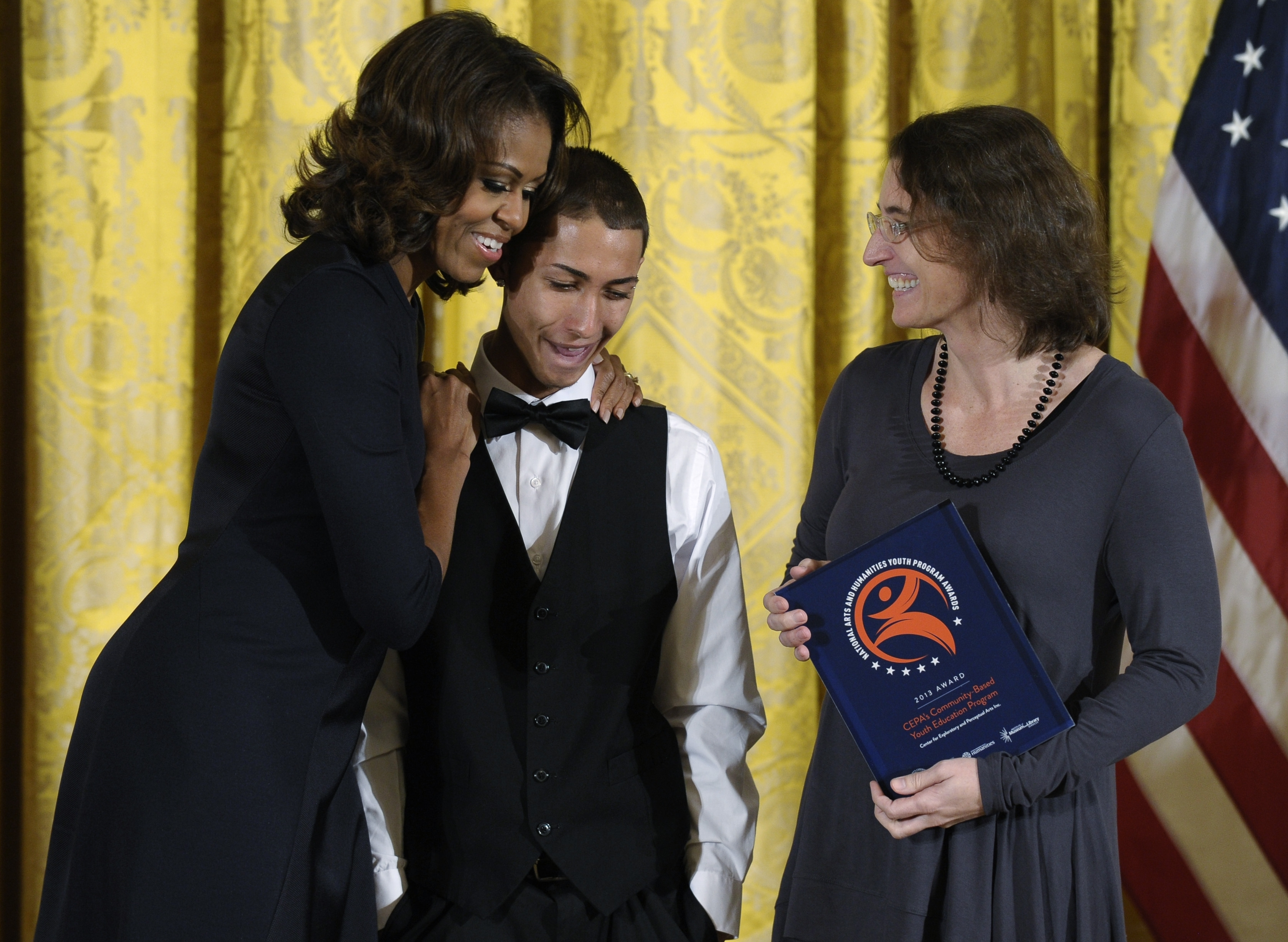 Jose Lagares, 18, center, gets a hug from first lady Michelle Obama, left, as Center for Exploratory and Perceptual Arts, Inc., Education Director Lauren Tent of Buffalo, N.Y., watches at right, at the White House in Washington, Friday, Nov. 22, 2013, where Lagares and Tent were presented with the Presidentís Committee on the Arts and the Humanities (PCAH) National Arts and Humanities Youth Program Awards. (AP Photo/Susan Walsh)