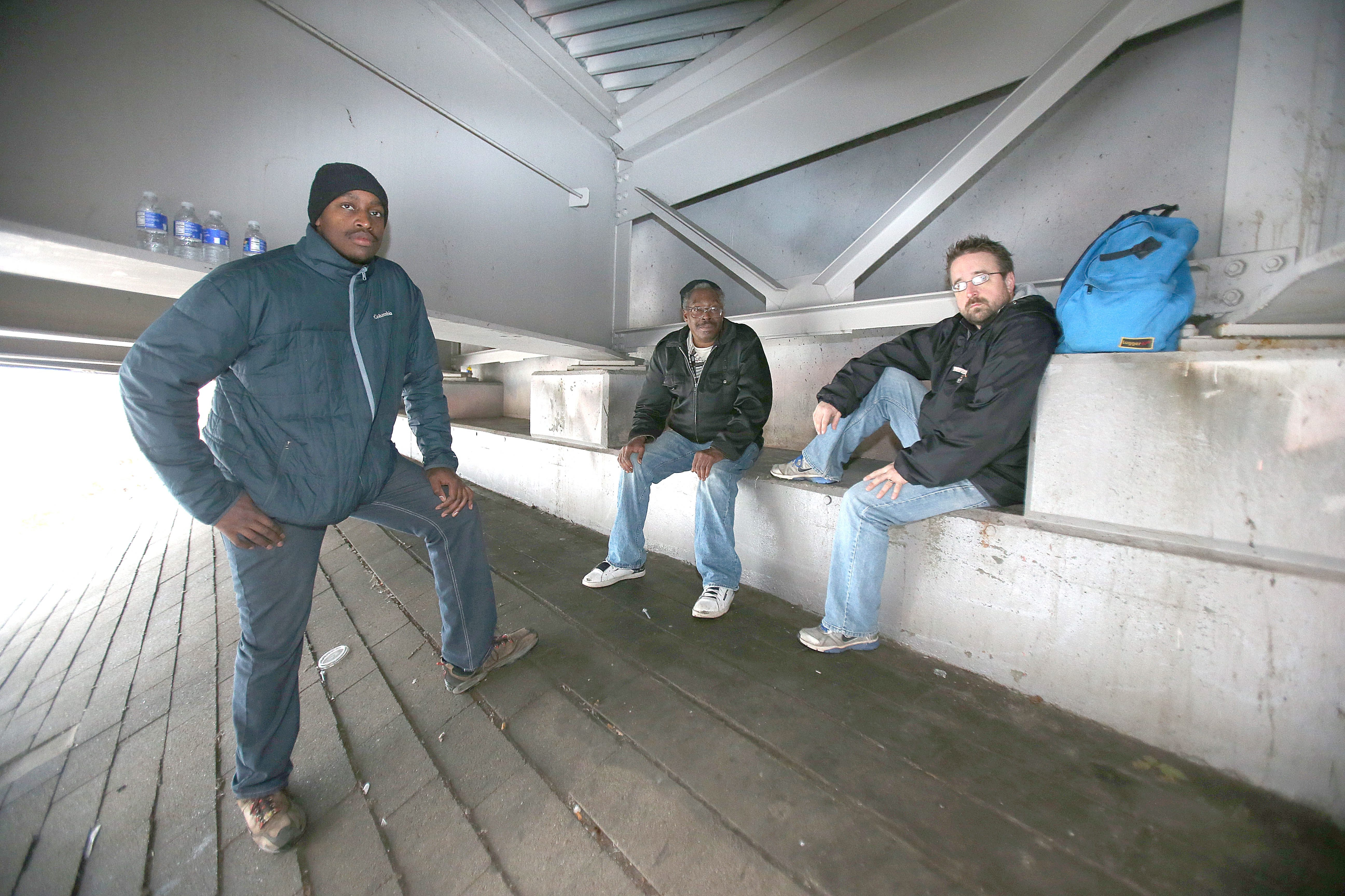 From left, John Jones, Keith Cauley and Rev. Eric Johns under the Michigan Avenue overpass of the Kensington Expressway on Friday .