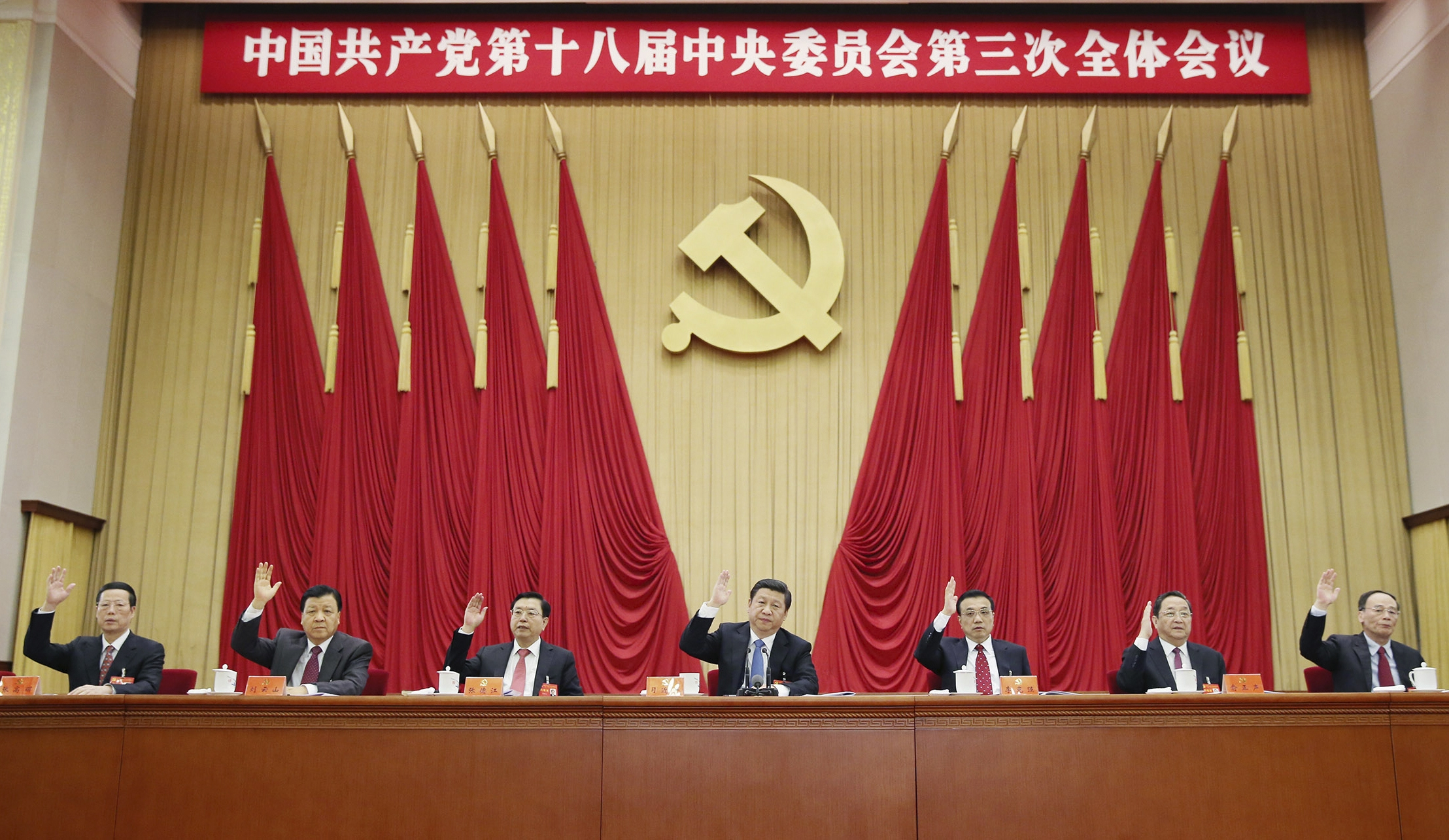 Chinese President Xi Jinping, center, and other Communist Party leaders raise their hands to vote in the Third Plenum of the 18th Central Committee of the Communist Party of China in Beijing on Tuesday.