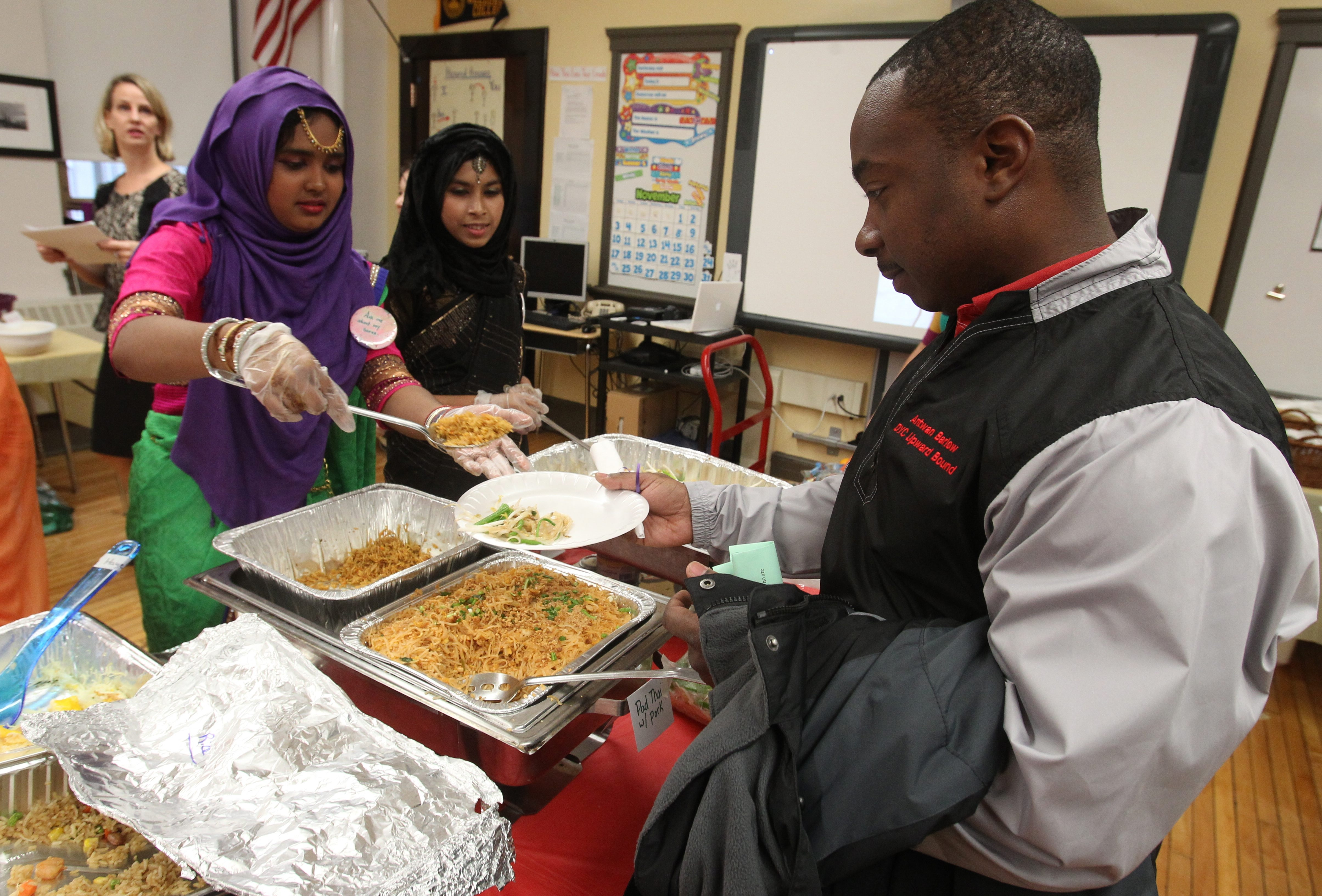Wahida Dipa, 17, left, and Afnan Ahmed ,18, serve food to Antwan Barlow as about 200 students share food and stories about their journey to America at the International Preparatory School  on Tuesday.