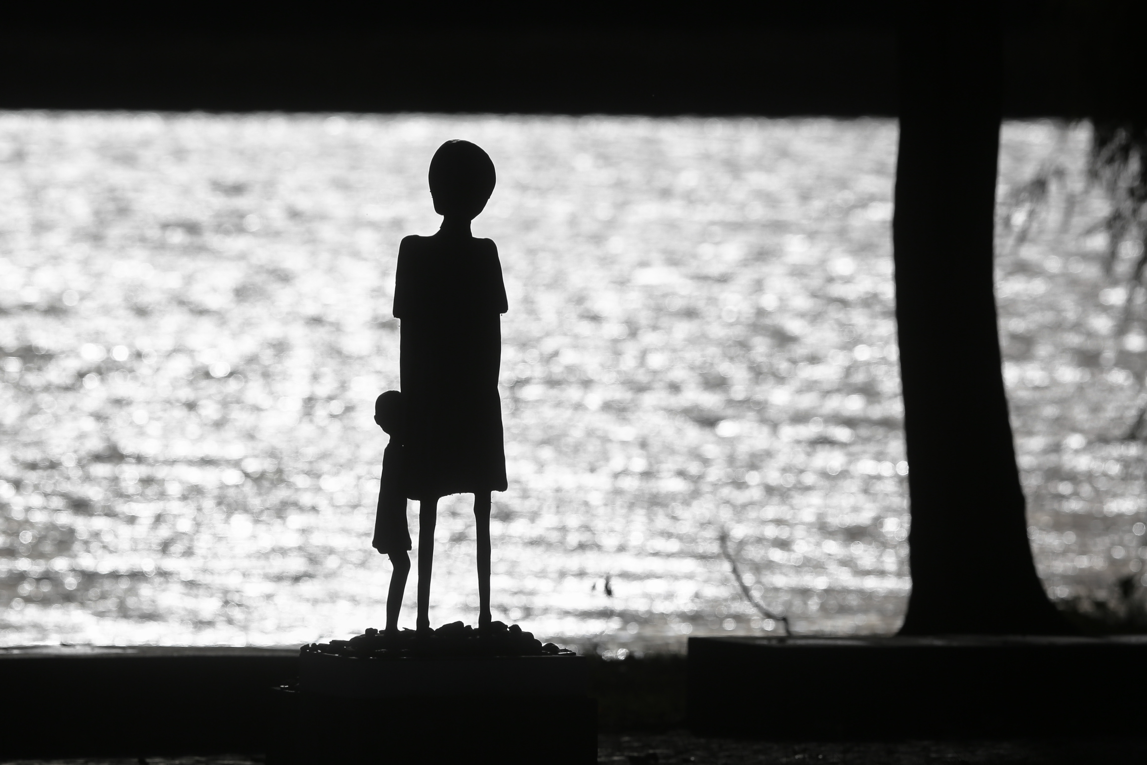 A sculpture of a woman and a child is silhouetted against the water of Schwedsee lake at Nazi death camp Ravensbrueck about 100 kilometers (62 miles) north of Berlin, Thursday, Nov. 7, 2013. On Nov. 9, 2013 Germany remembers the 75th anniversary of the 'Kristallnacht', 'Night Of The Broken Glasses' or 'November Pogrom'. On Nov. 9, 1939  the Nazis coordinated a wave of attacks in Germany and Austria, smashing windows, burning synagogues, ransacking homes and looting Jewish-owned stores. (AP Photo/Markus Schreiber)