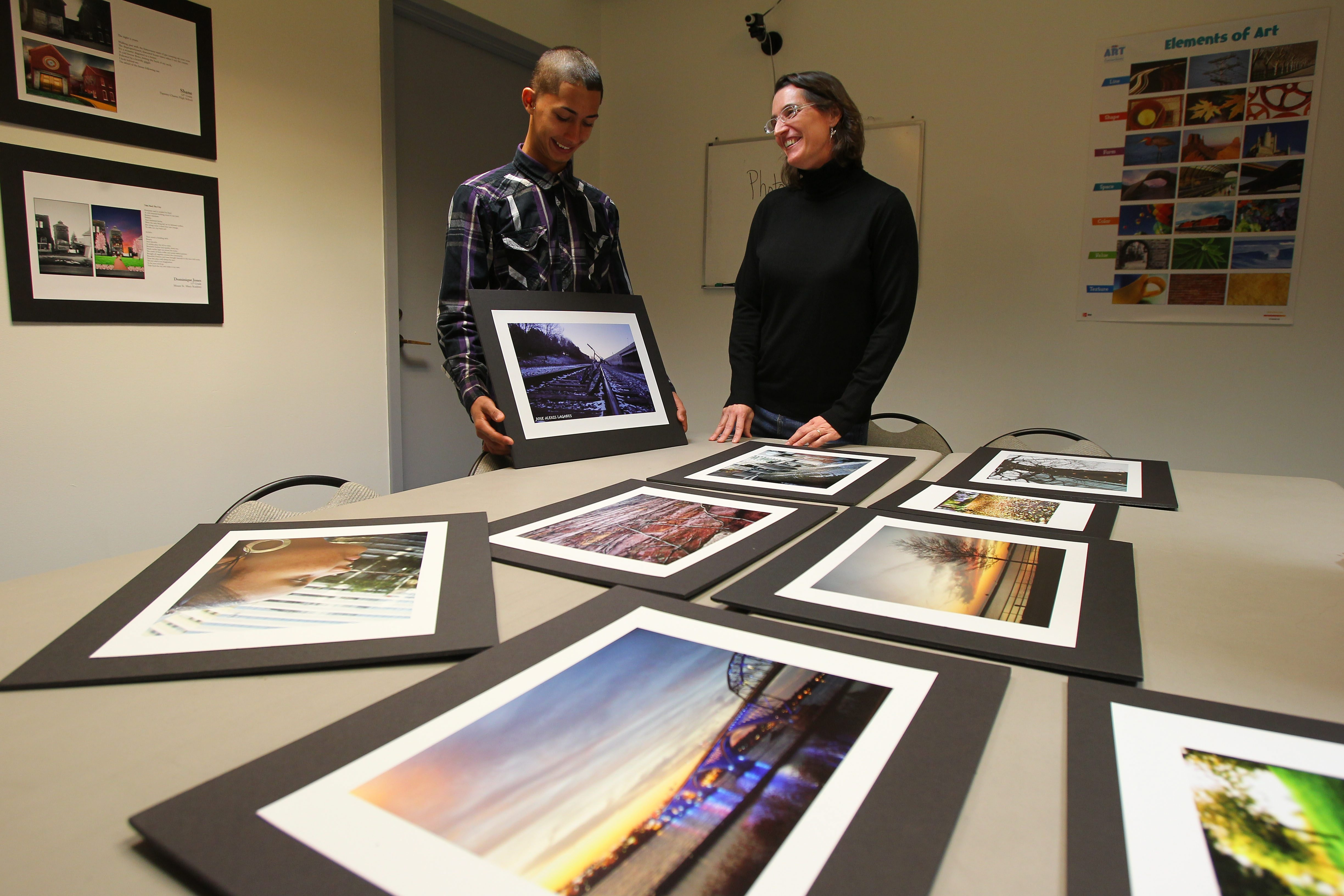 Jose Lagares and CEPA Education Director Lauren Tent look over some of his photographs at the CEPA Gallery in Buffalo on Tuesday. They'll be meeting Michelle Obama at the White House on Friday.
