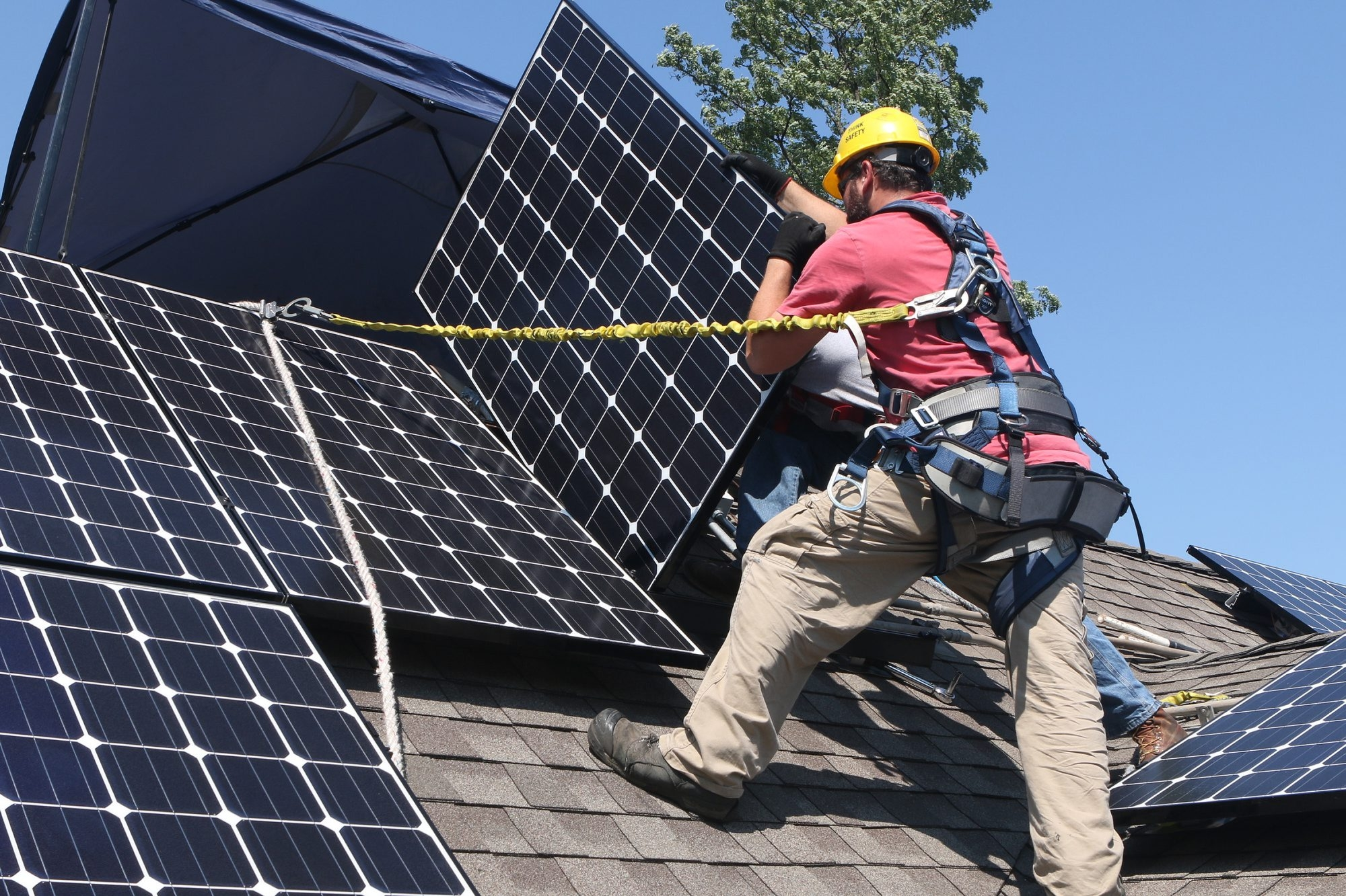 Workers install Solar Service Inc. photovoltaic solar electric panels on the roof of a home in Park Ridge, Ill.
