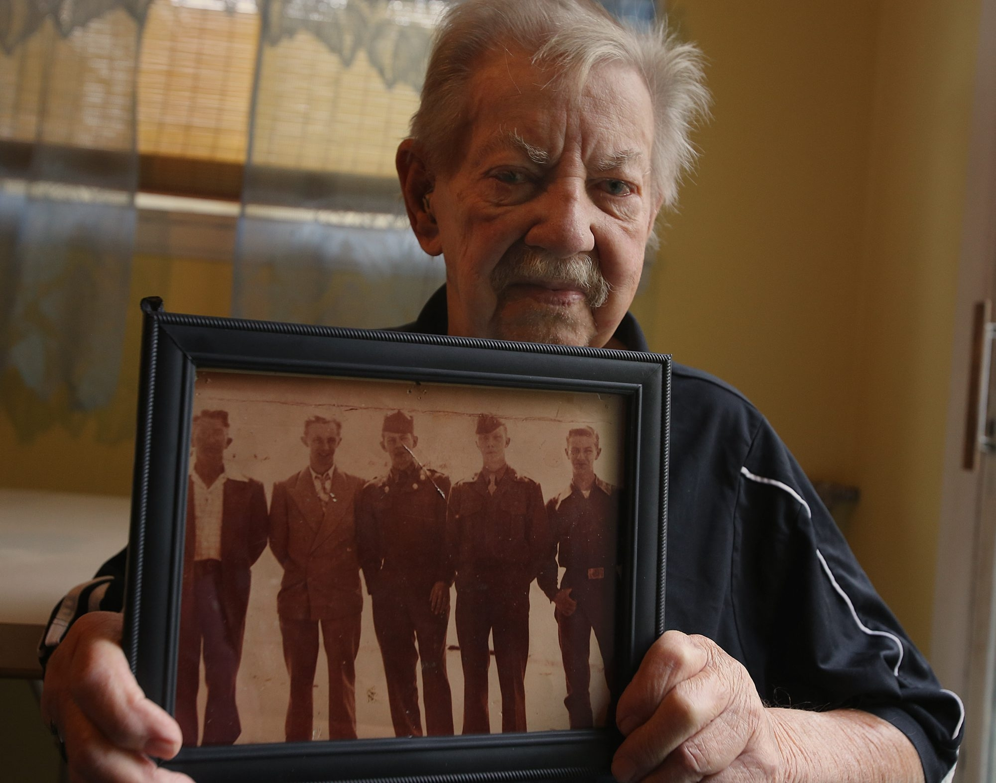Robert E. Yale, of Buffalo, veteran of WWII occupation and Korean War, showing photo of him at center with, from left, father Leonard Sr. and brothers Leonard Jr., Carl and Keith.