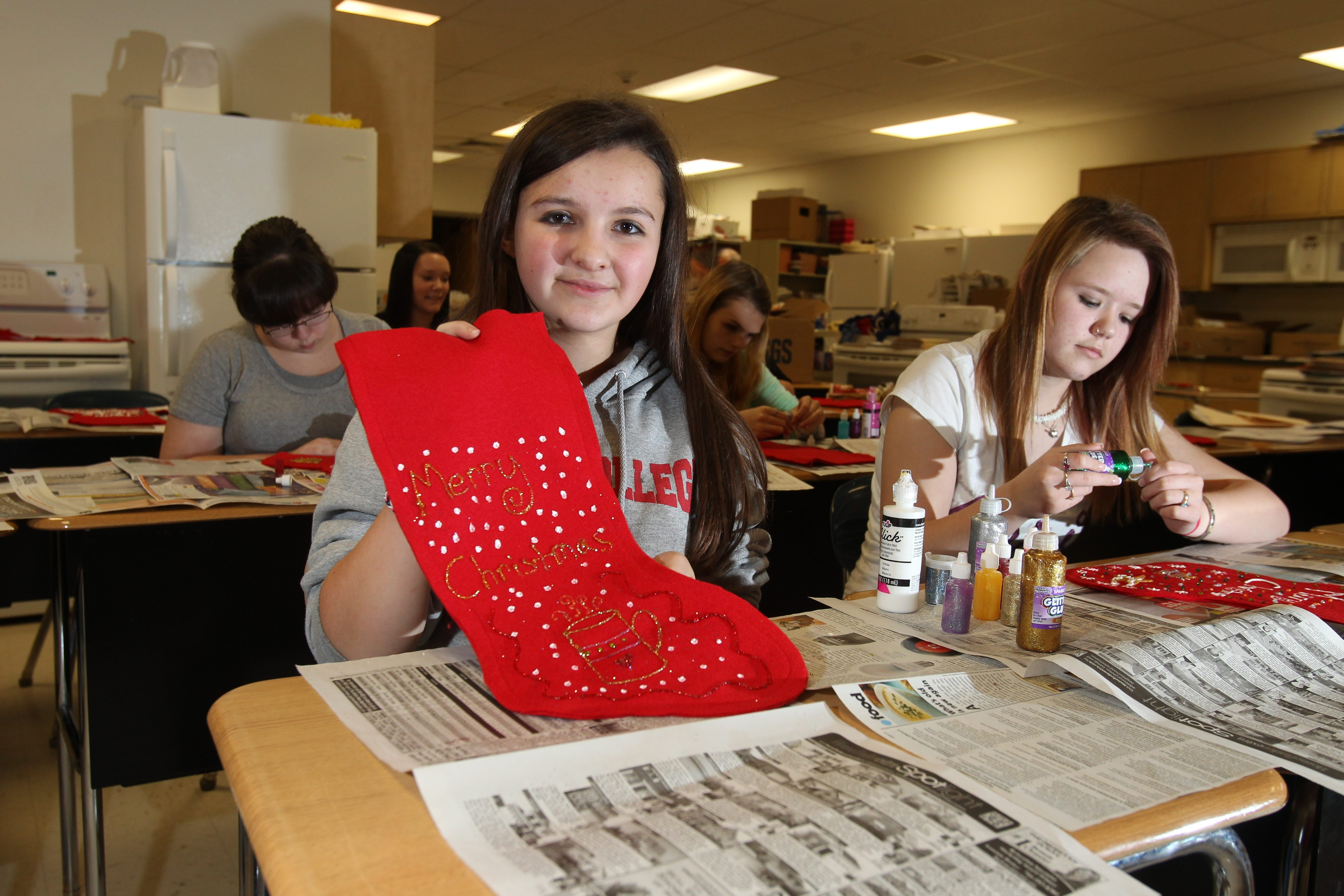 Kallie Olear, left, and Mariah Miller, both 15, members of  Deborah Sweeney's family and consumer science class at Wilson High School,  decorate Christmas stockings for soldiers and their families.