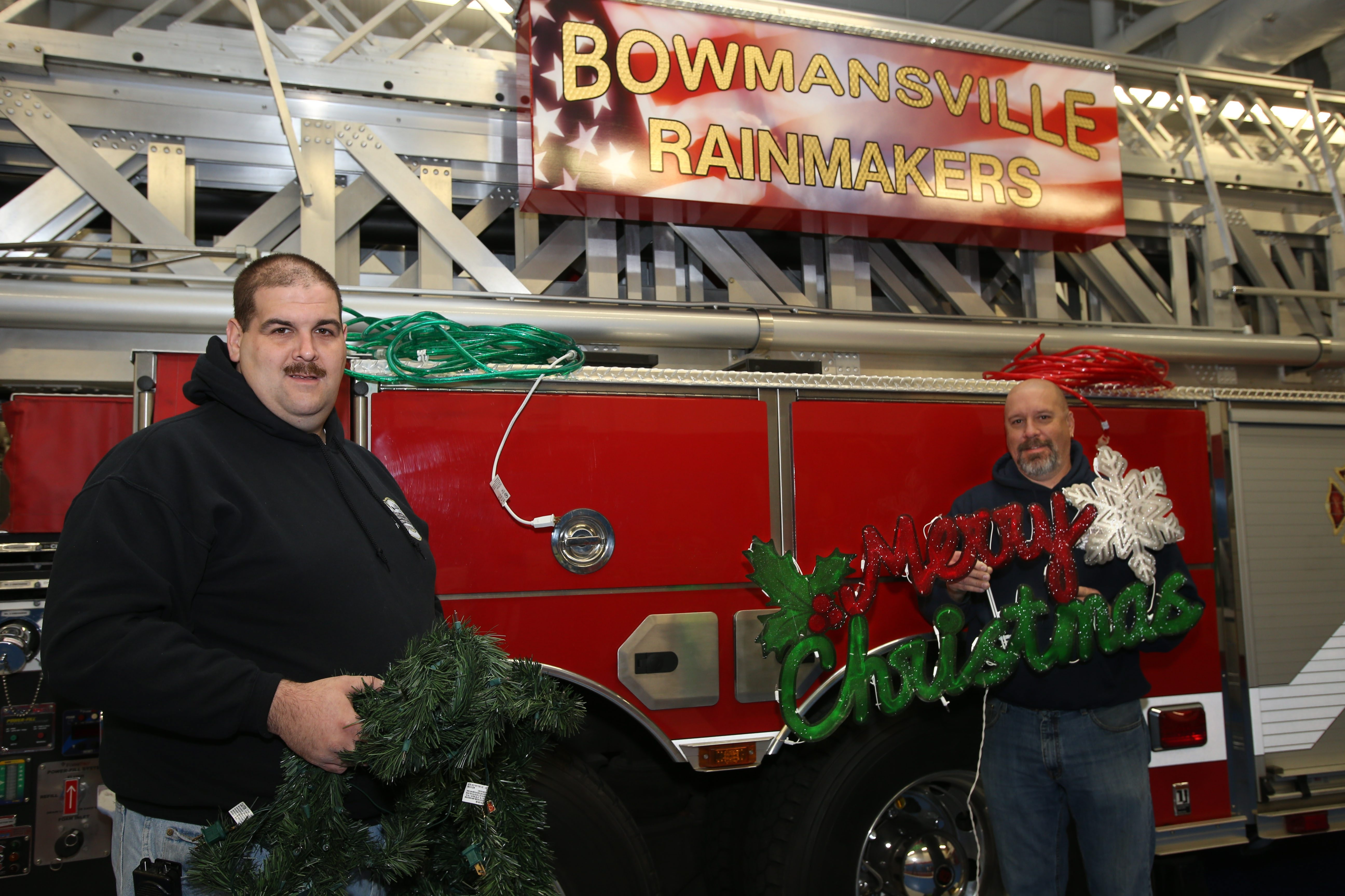 Firefighters Tom Trzepacz, left, and Jerry Enser, co-chairmen of the sixth annual Christmasville Fire Truck Parade, prepare to decorate the ladder truck at the Bowmansville Fire Station on Thursday. The parade will take place on Saturday.