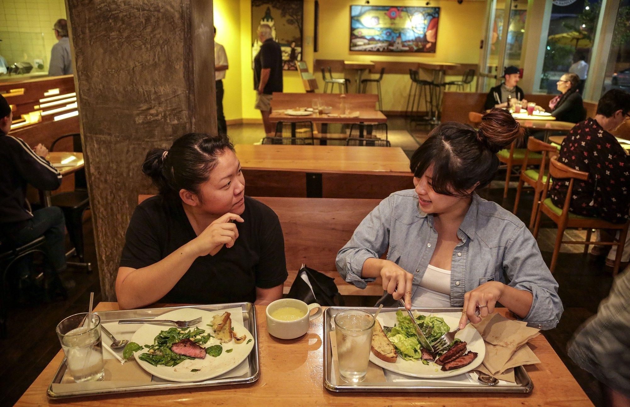 Johanna Tchon, left, and friend Jane Moro enjoy a meal of flatiron/backyard steak at Tender Greens in Pasadena, Calif.