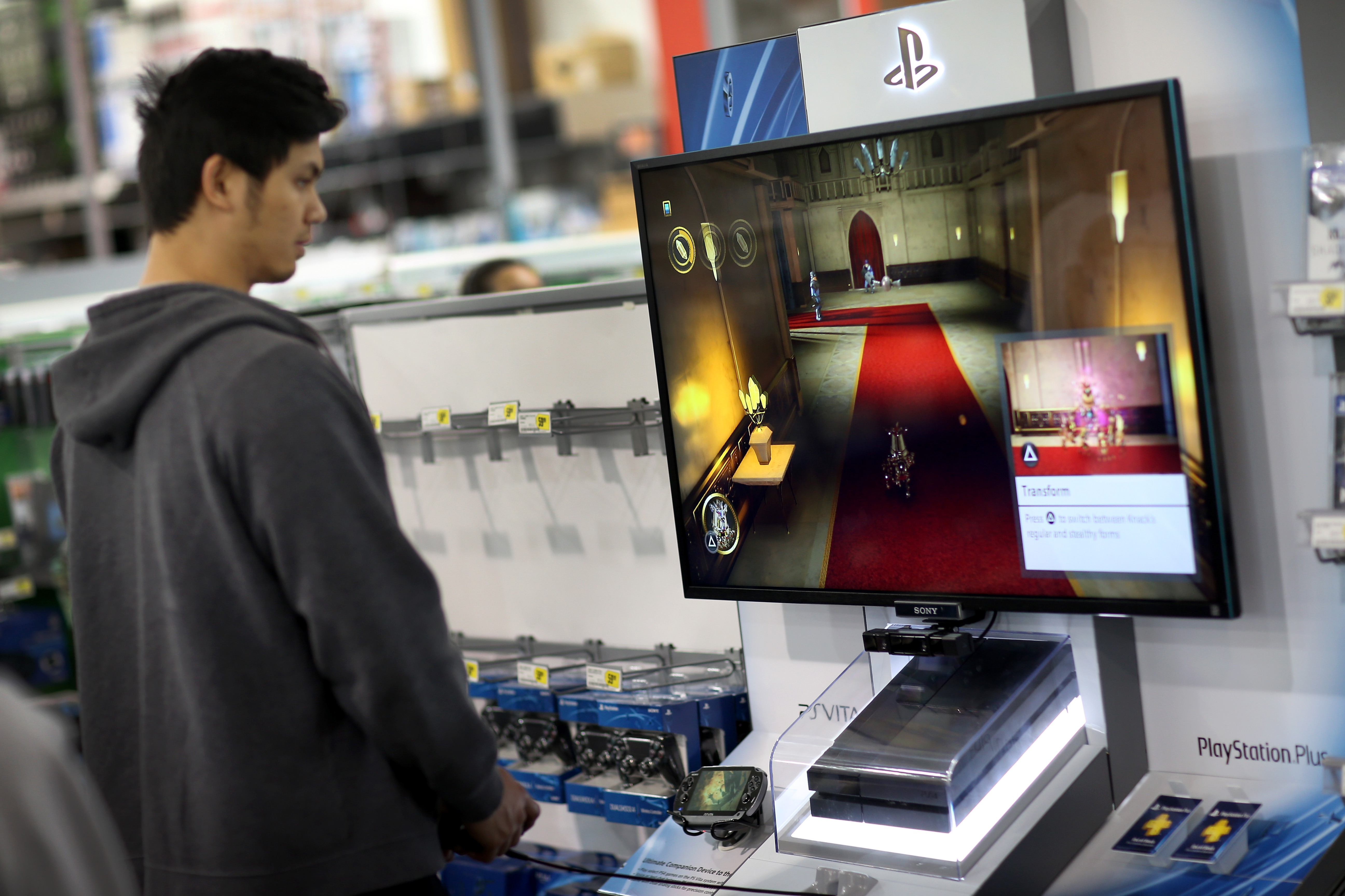 PEMBROKE PINES, FL – NOVEMBER 15: Dennis Lacson plays the new Sony Playstation 4 that is on display at Best Buy after they went on sale at midnight on November 15, 2013 in Pembroke Pines, Florida. PlayStation 4 is the follow-up to the company's PlayStation 3 and is priced at $400.  (Photo by Joe Raedle/Getty Images)
