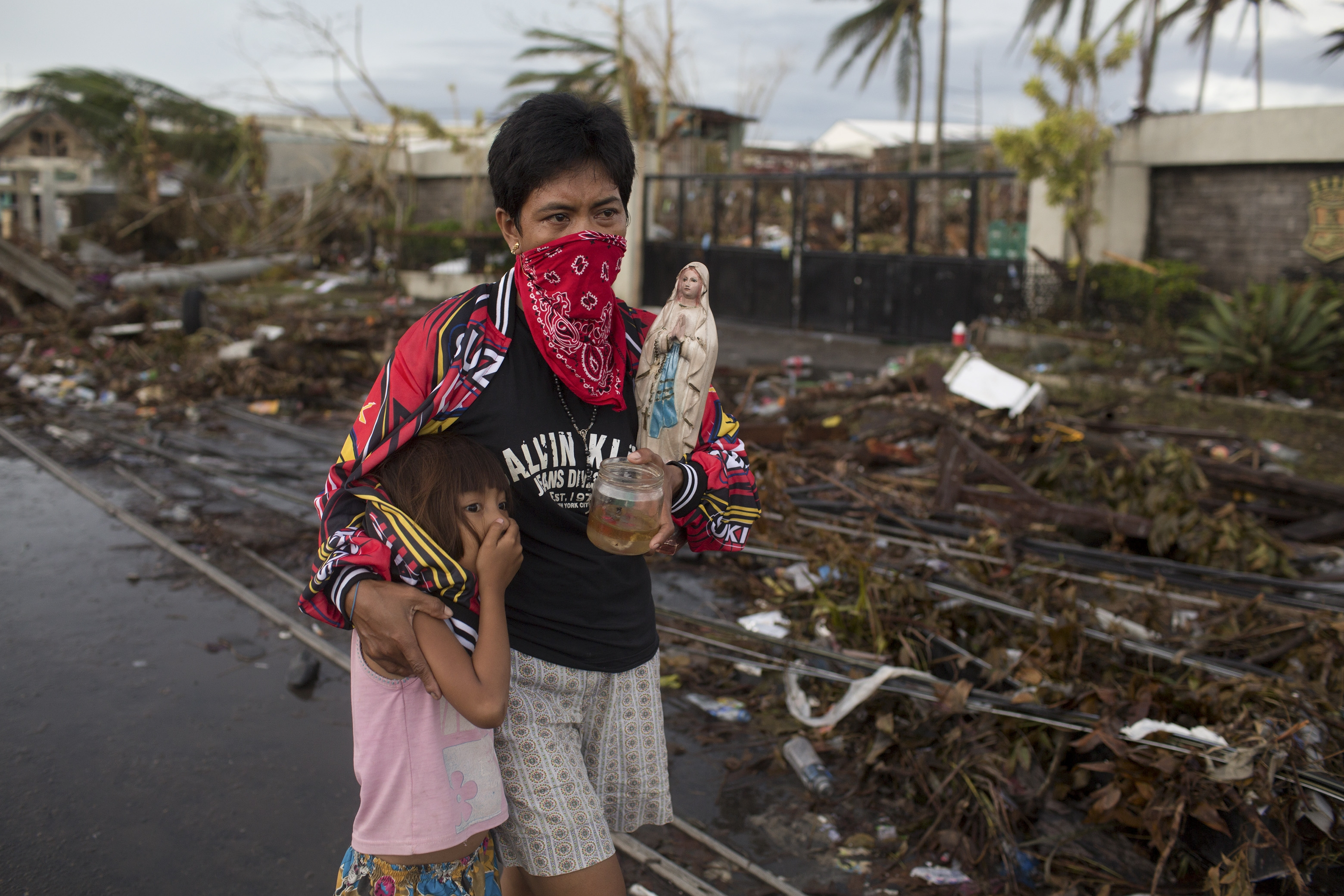 Filipinos cover their noses as they carry a few belongings out of devastated Tacloban.