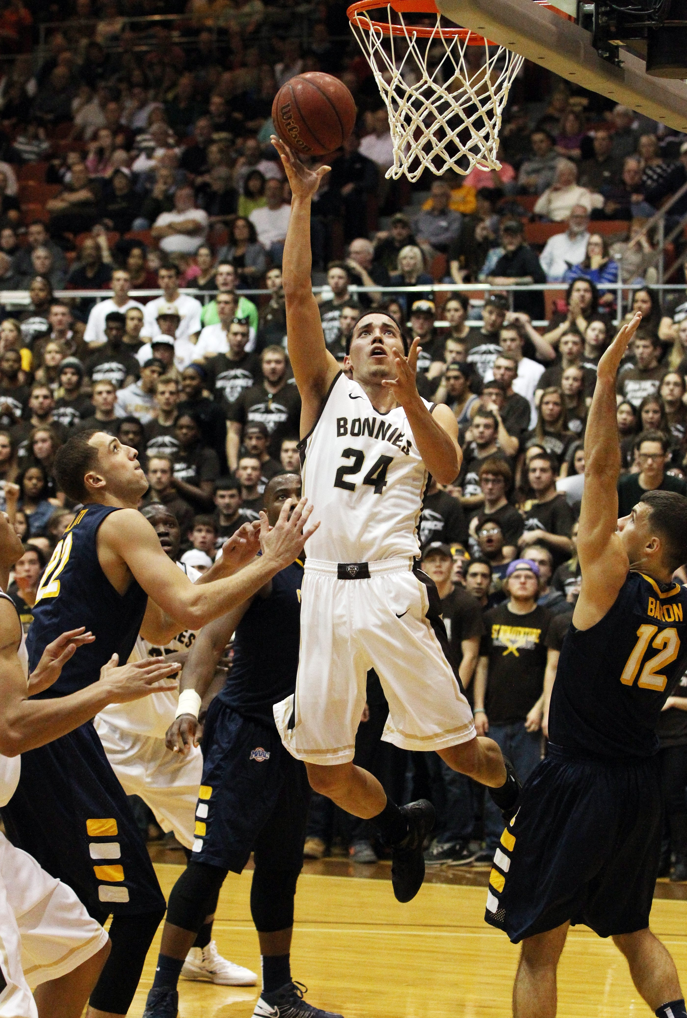 Bonnies guard Matthew Wright scores two points over Golden Griffins guard Billy Baron as St. Bonaventure secured its first 3-0 start in 13 years with the win over Canisius.