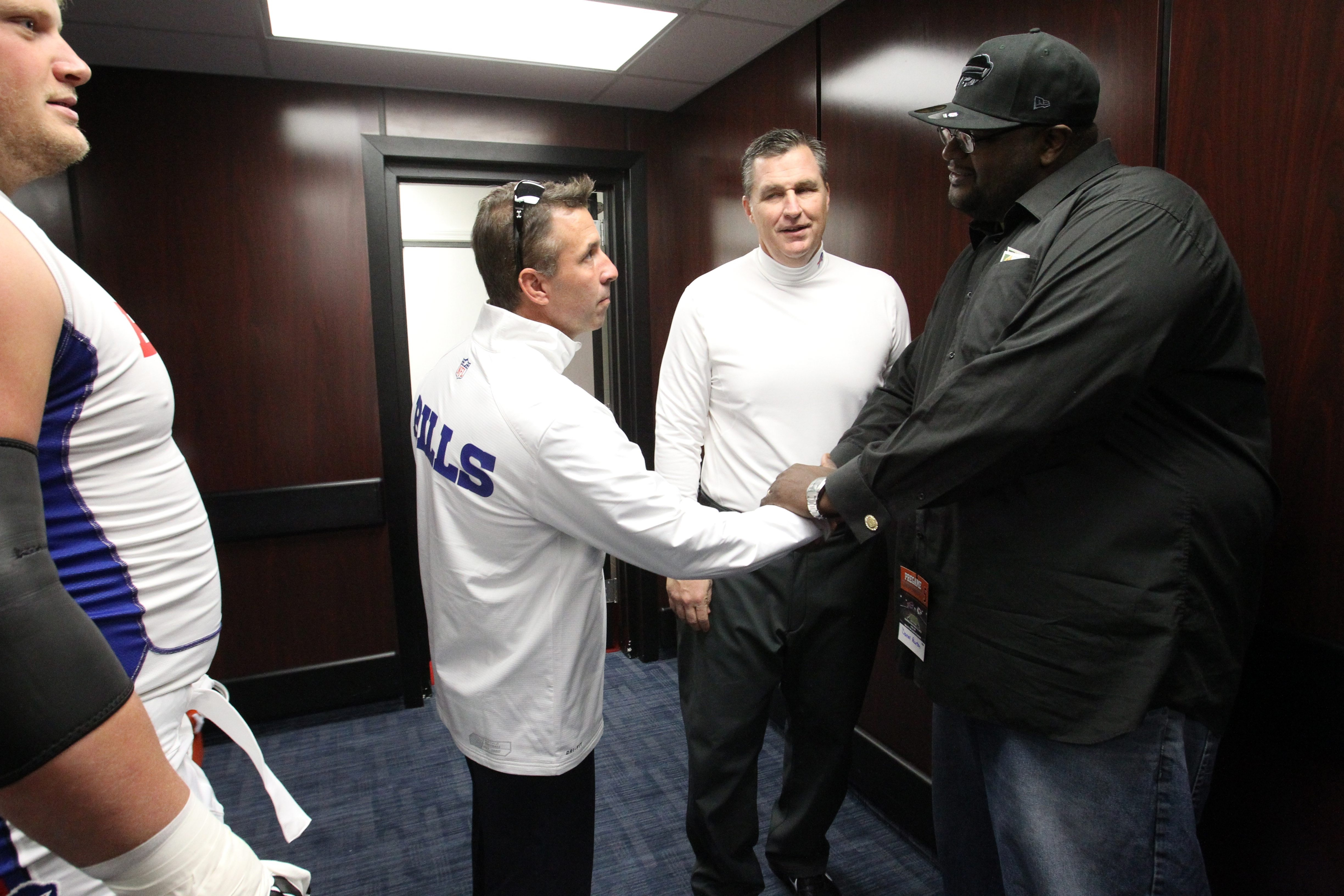 Russ Brandon (left), president and chief executive officer of the Buffalo Bills, and head coach Doug Marrone (center) invited Darnell Barton, the Metro bus driver who saved a woman's life, into the locker room before today's game at Ralph Wilson Stadium.