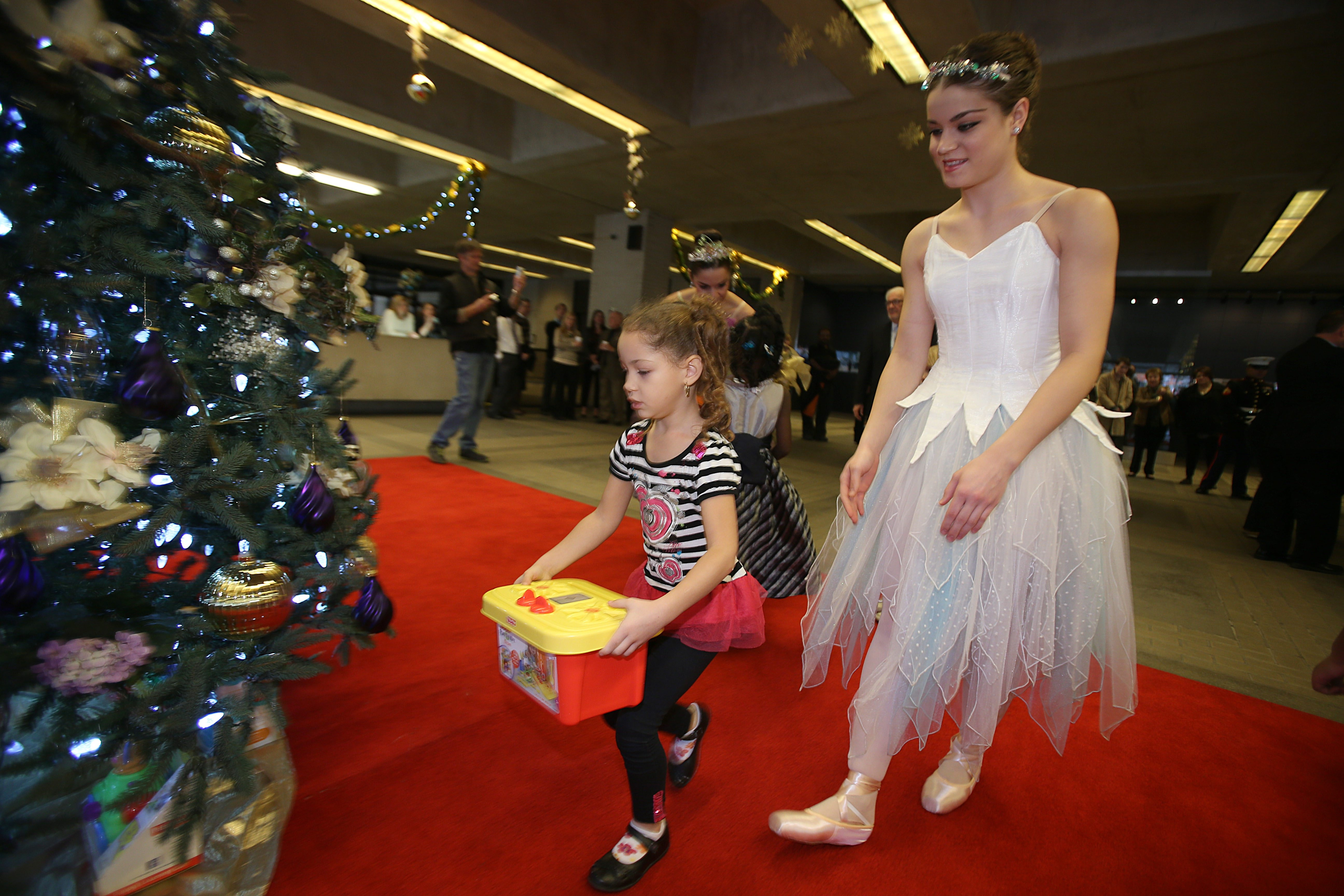 Houghton Academy student Amaree Workman, 5, is assisted by Neglia Ballet dancer Marie Keil, as she places a gift during the tree lighting ceremony in the lobby of the Buffalo News, Thursday.