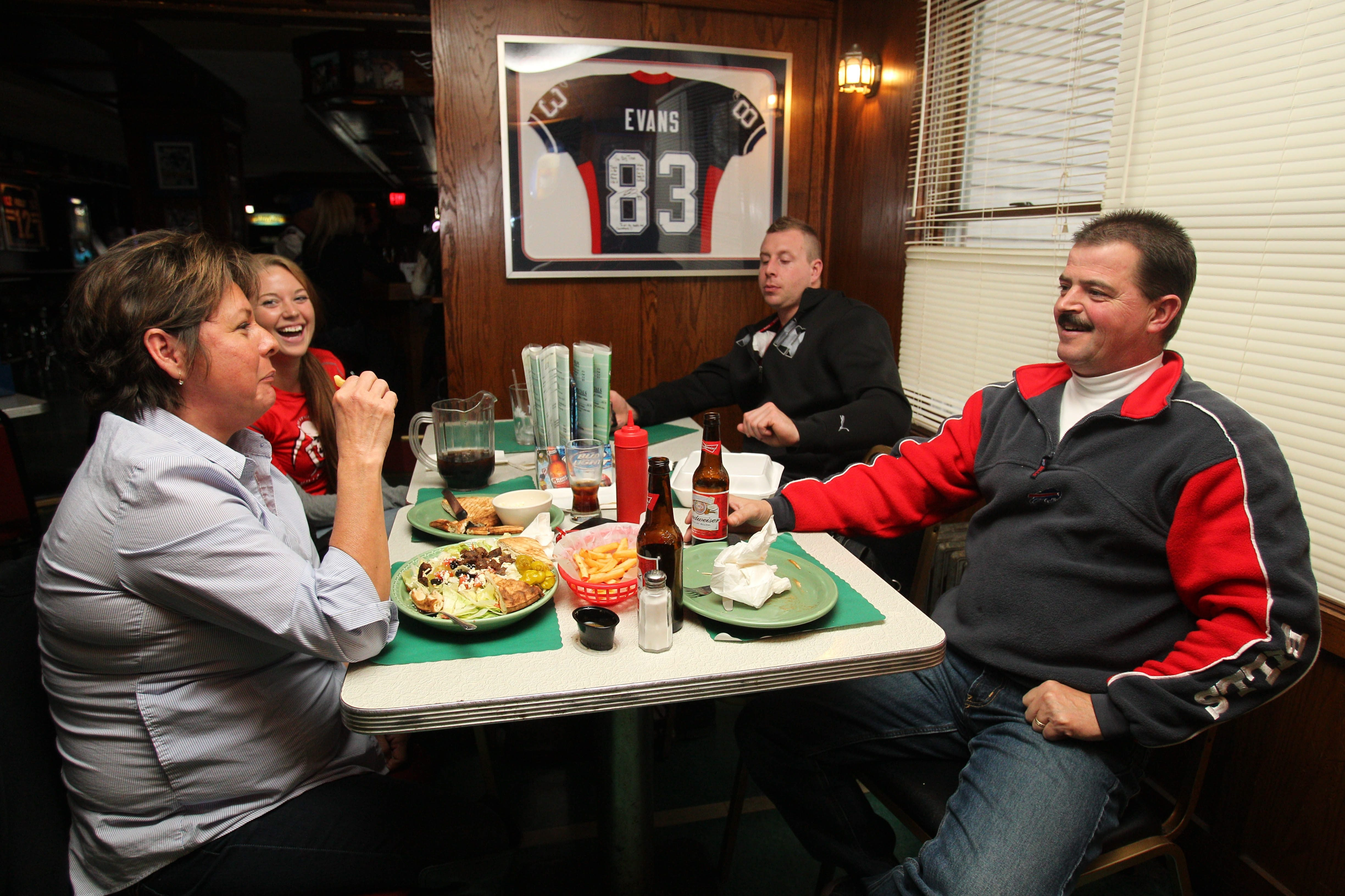 Customers watch the Bills game at the Big Tree Inn on Abbott Rd. in Orchard Park, Sunday, Nov. 10, 2013.  Helen Hout, left, and her husband Jim, right,  are accompanied by their son Andrew Clark, second from right and his girlfriend Jennifer Riccuti.  They are from the Town of Niagara. (Sharon Cantillon/Buffalo News)