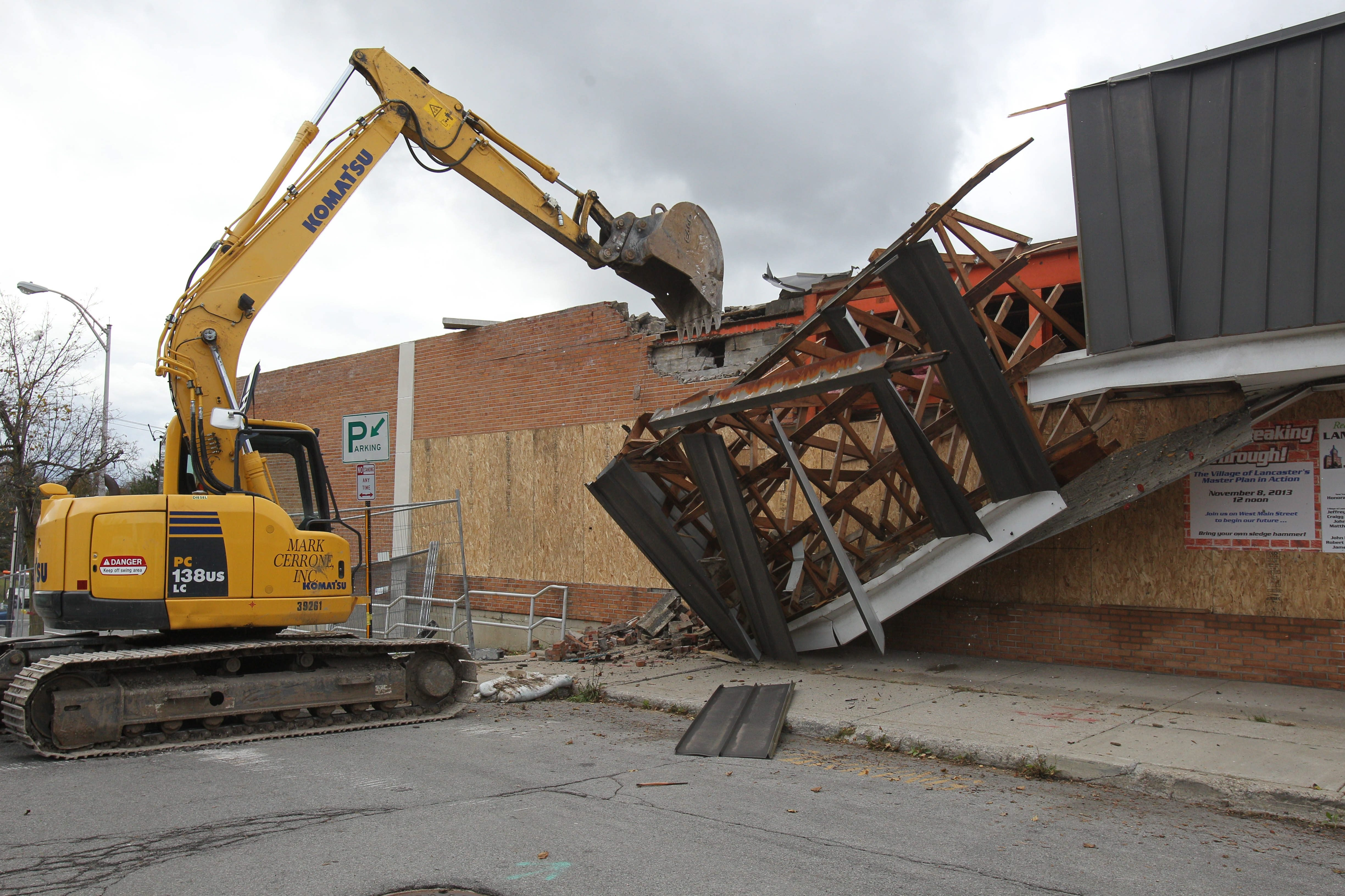 An excavator works to knock down the front wall of the Lancaster Village Partnership Complex at the end of West Main Street in Lancaster on Friday.