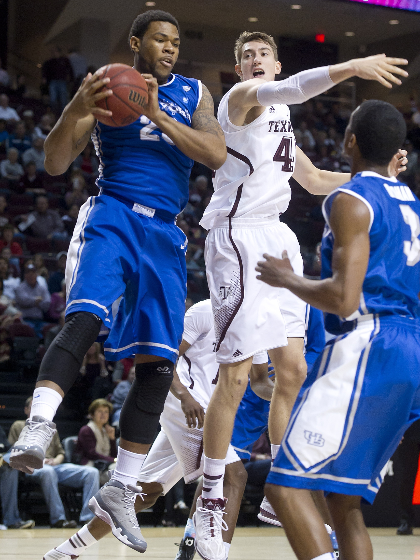 Buffalo's Justin Moss, left, pulls in the rebound against Texas A&M's Dylan Johns in Friday's game.