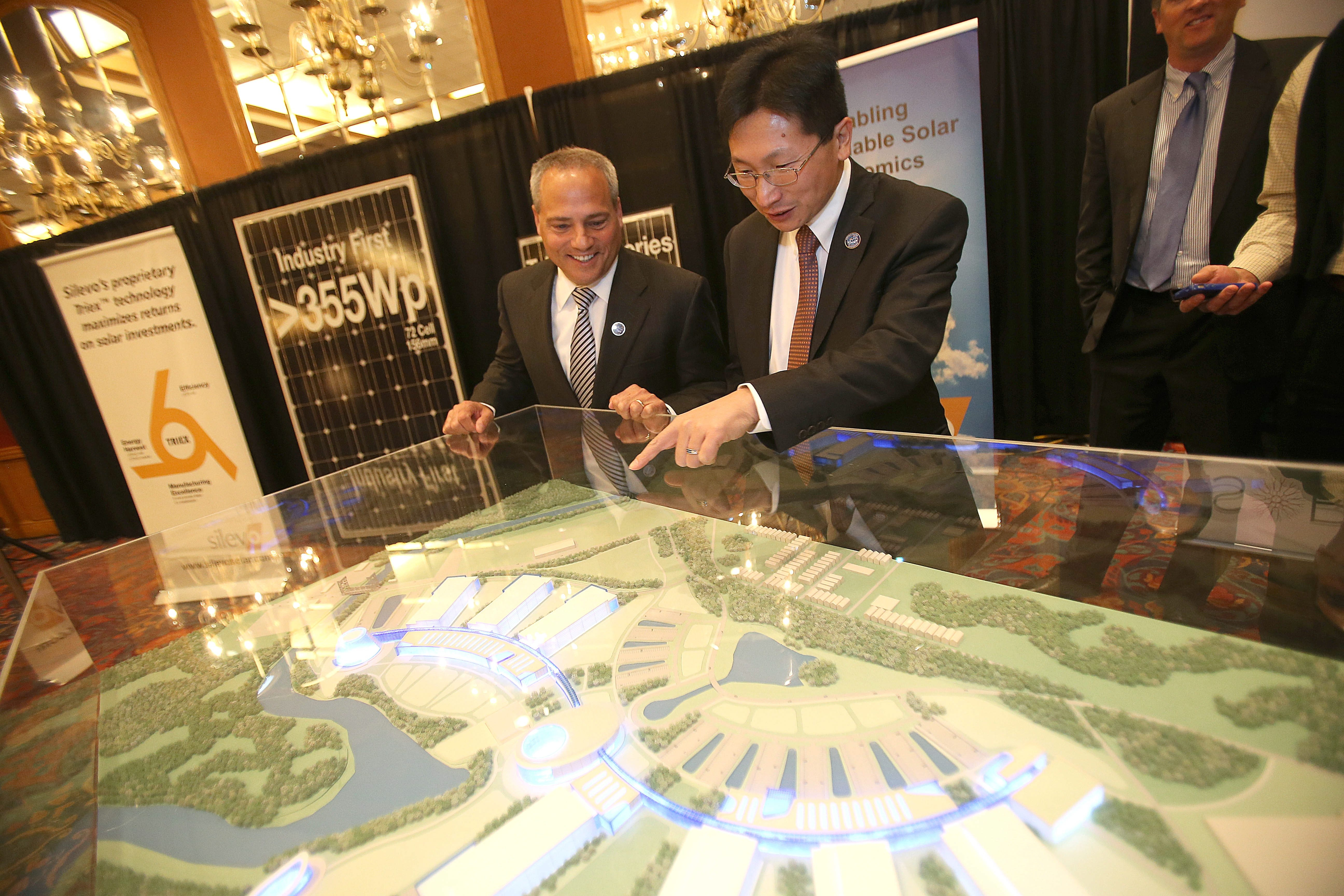 Dr.  Caulfield, president and COO of Soraa, left, and Dr. Zheng Xu, CEO of Silevo look at the 3D model of the river bend project after the announcement today at Adam's Mark Hotel today on Thursday, Nov. 21, 2013.  (Robert Kirkham/Buffalo News)