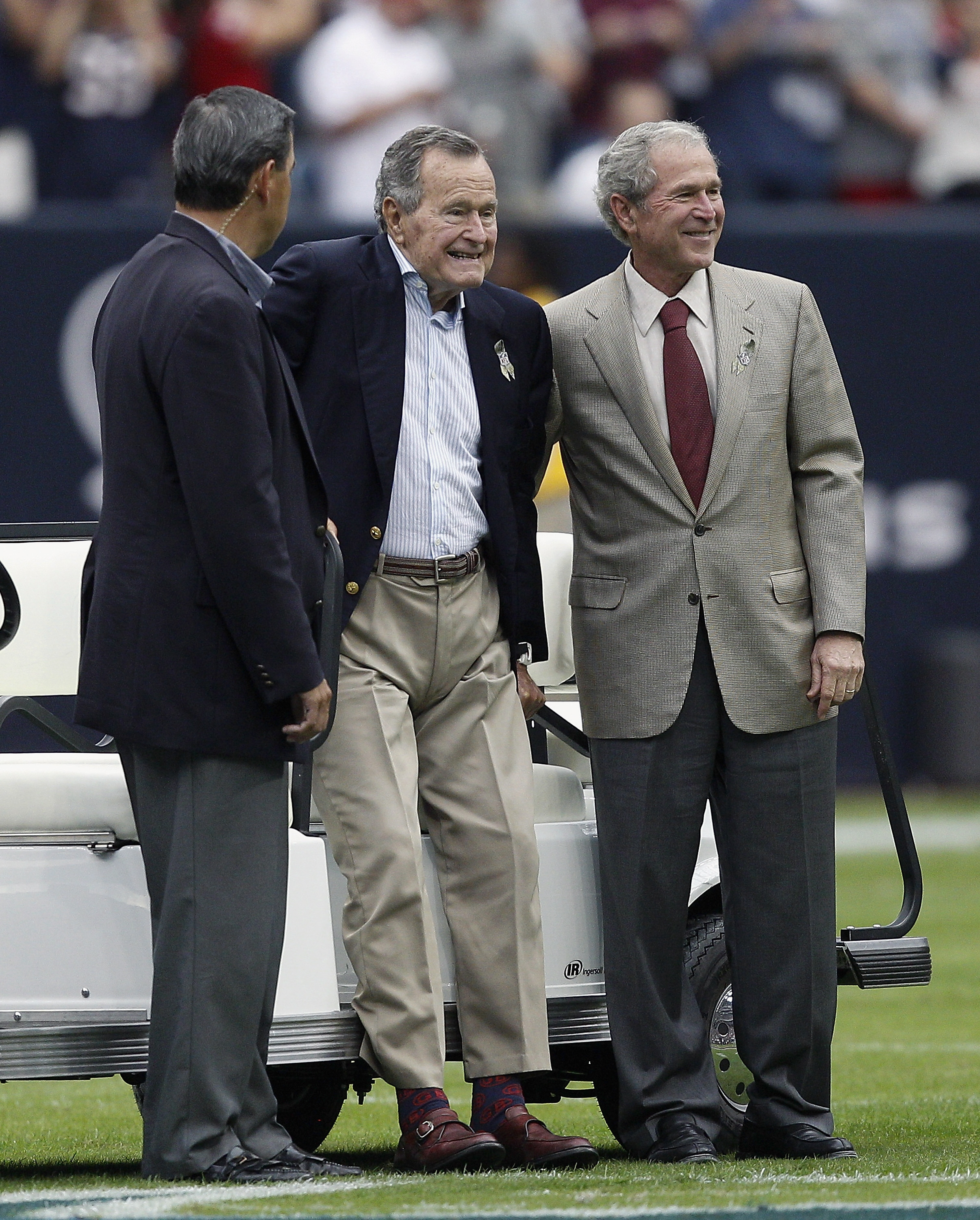 Father-son outing: Former Presidents George H.W. Bush, center, and George W. Bush, right, attended Sunday's game between the Oakland Raiders and Houston Texans in Houston.