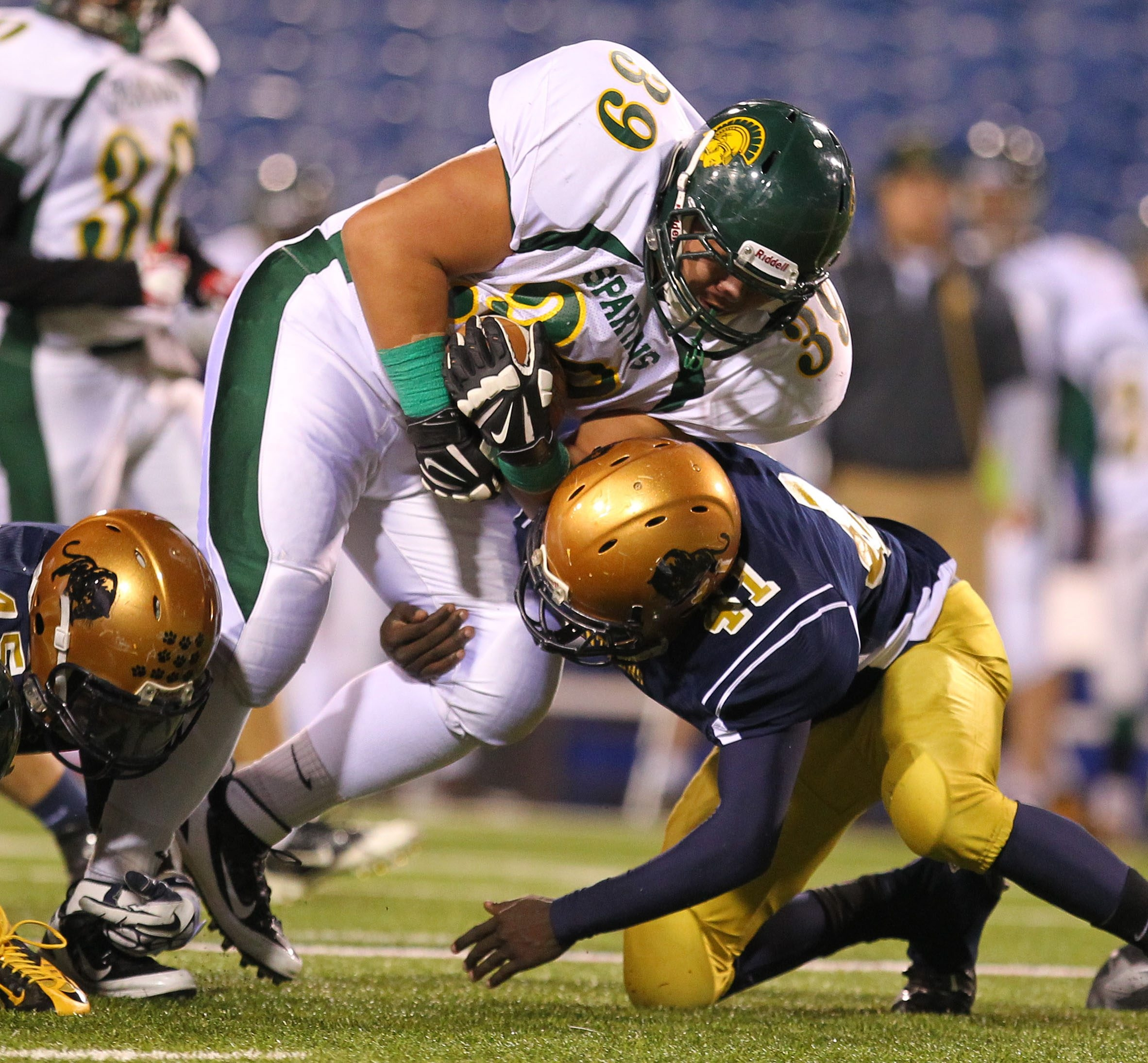Williamsville North's Duke Hwang tries to run over Sweet Home's Milton Ziegler during the first half of the Section VI Class A final at Ralph Wilson Stadium on Friday.