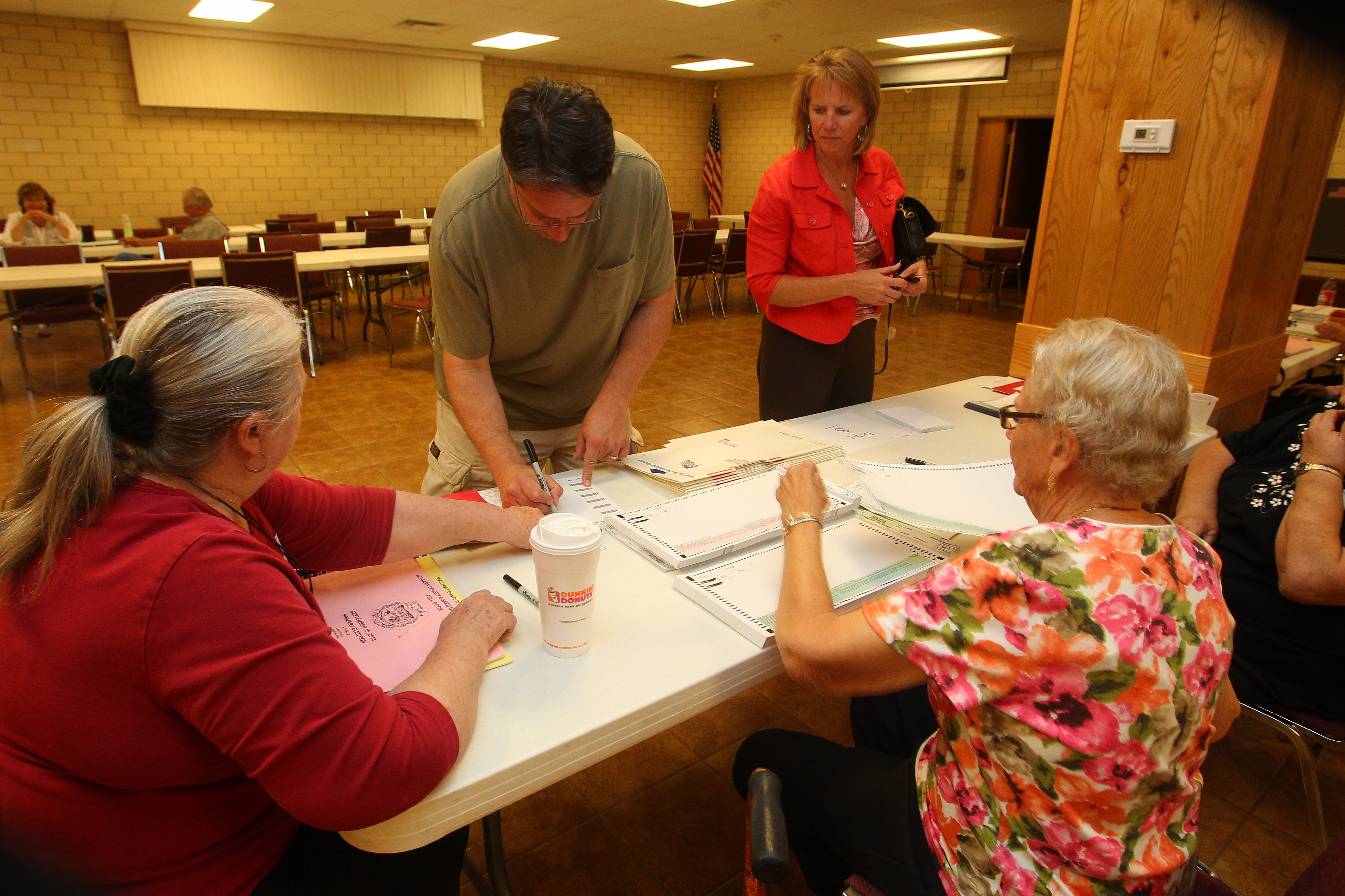 Elections inspector Virgina Boone, left, assists Leo Notaro, and elections inspector Elaine Pfohl helps Barb Walck in the primary election at Town of Niagara Active Hose on Sept. 10. They will be back in action Tuesday.